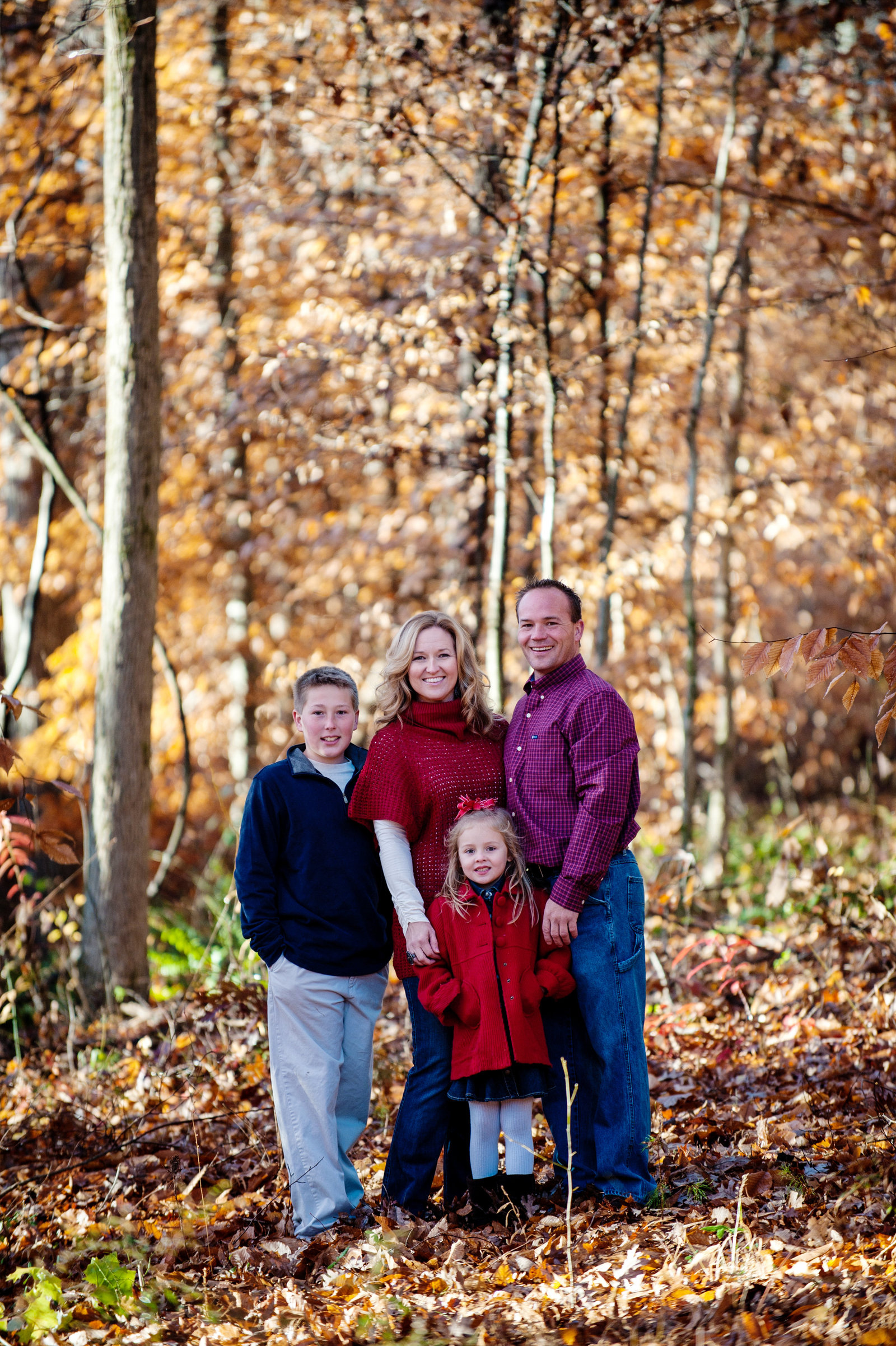 a family of four pose together in a forest in autumn
