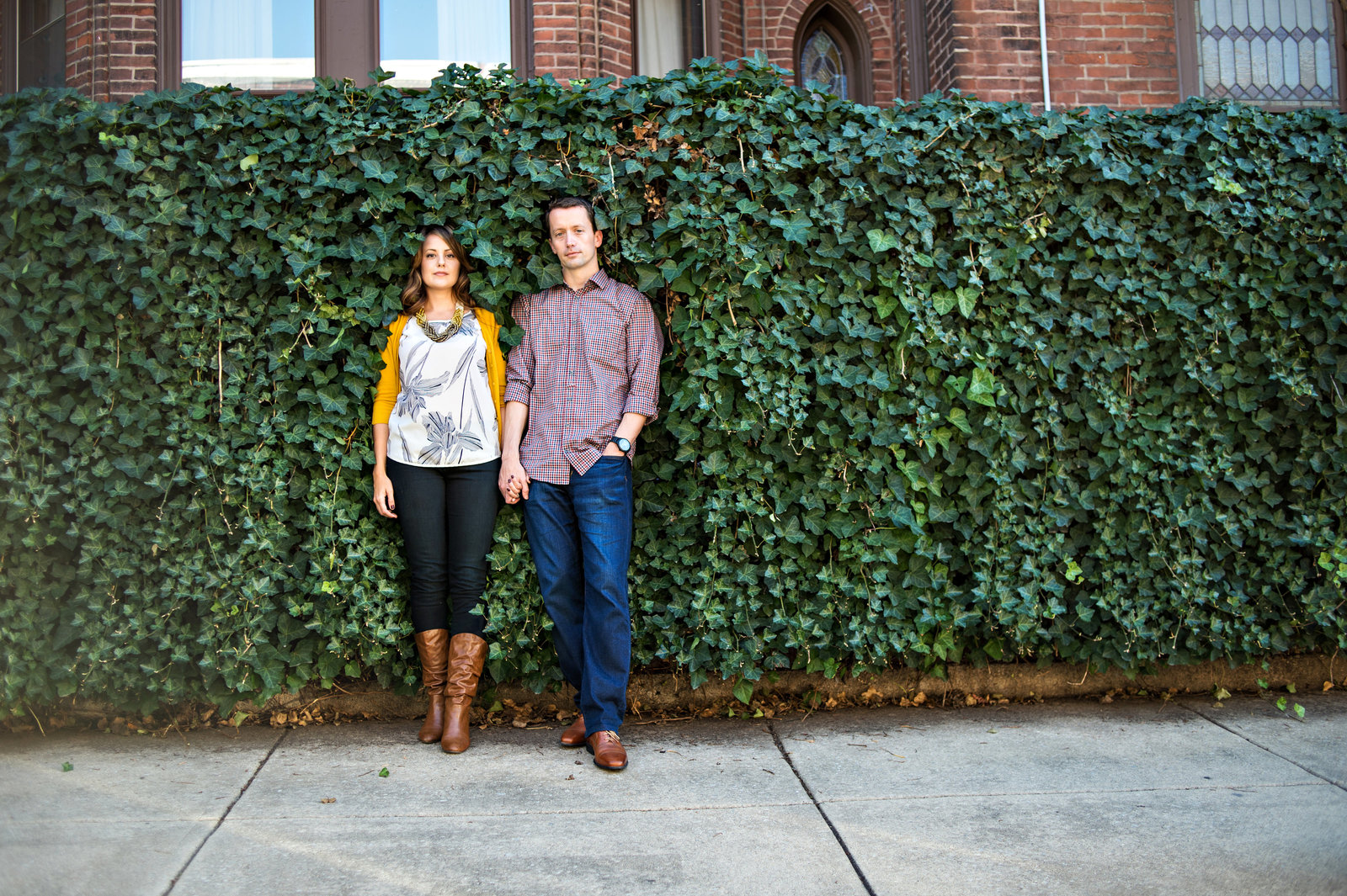 A couple hold hands in front of a wall covered with vines.