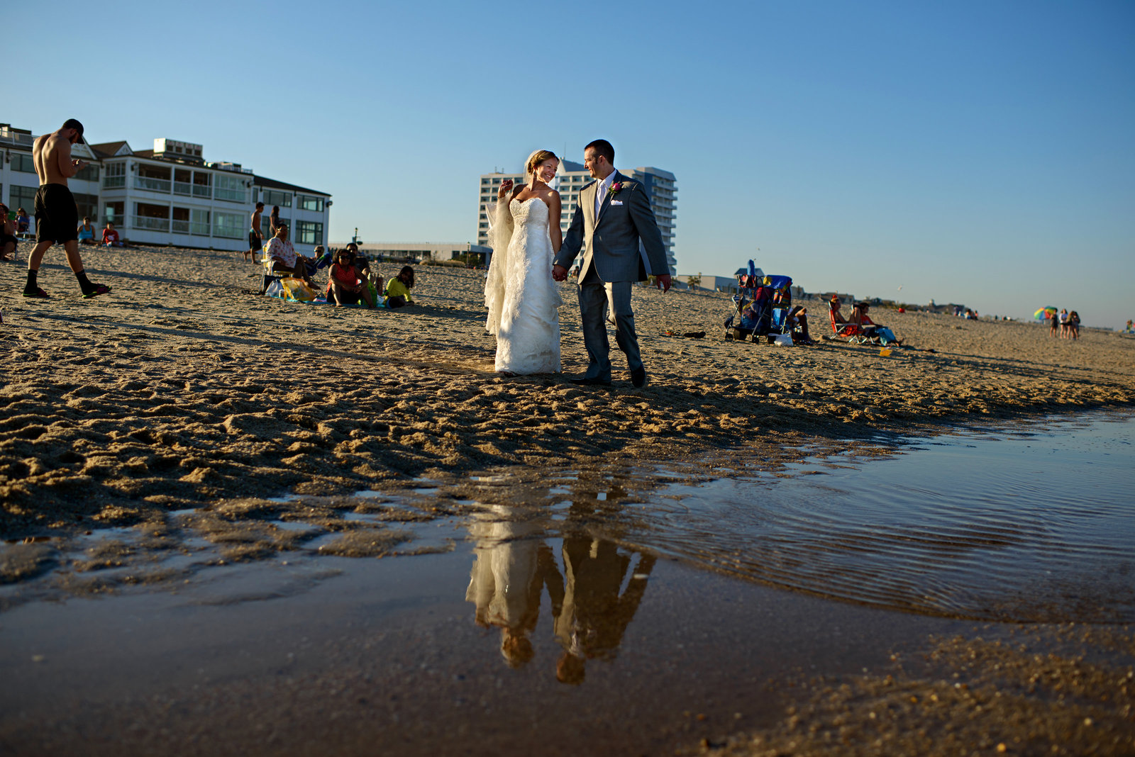 A newly married couple walk along the beach after their long branch NJ wedding.