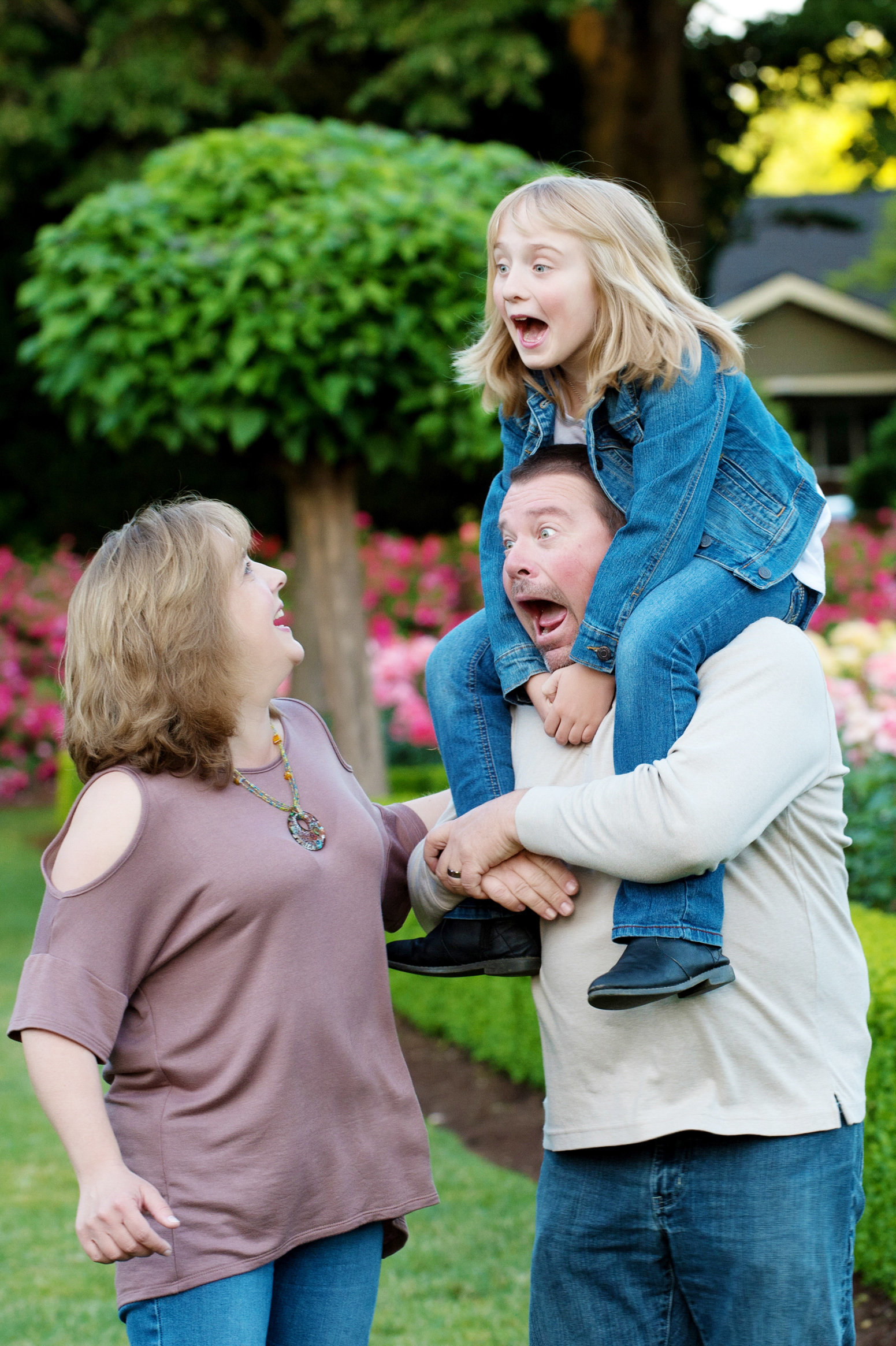 a dad holds his daughter on his shoulders and they both make funny faces at mom