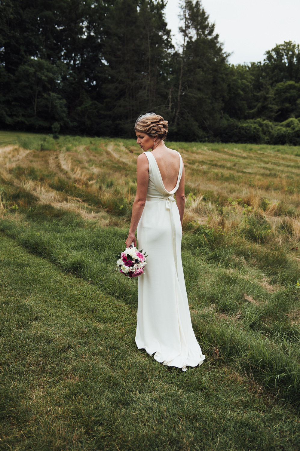 Bride standing in a field behind Brantwyn Estate