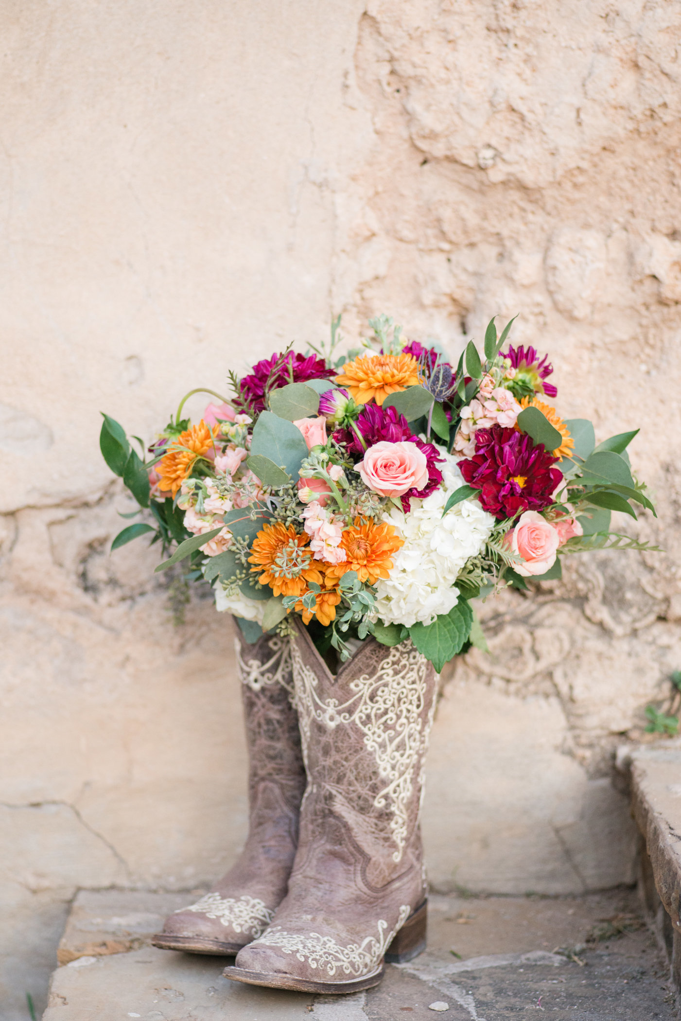 Fall Wedding bouquet in jewel tones stands inside bridal cowboy boots in Texas