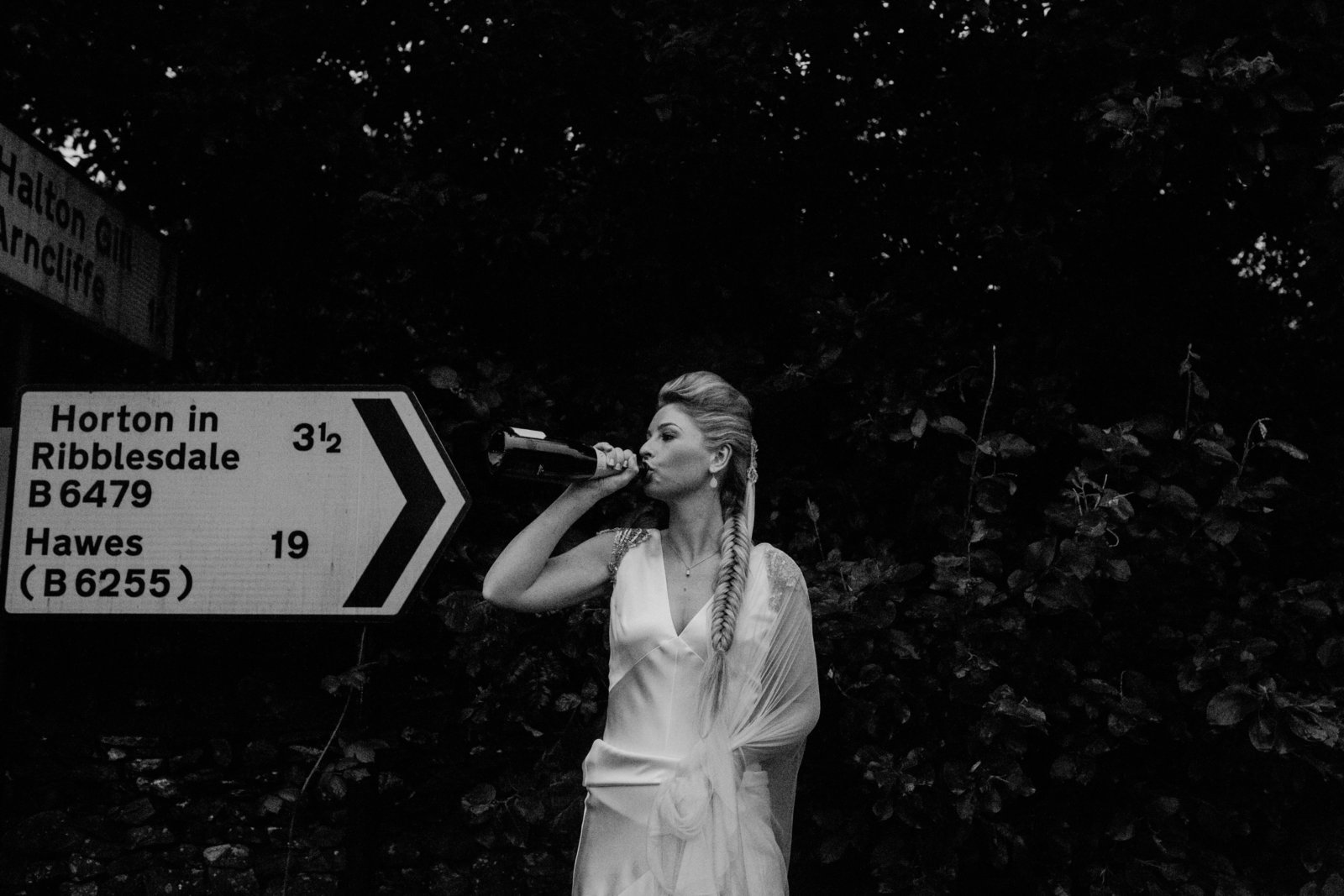 Bride drinking champagne at Taitlands wedding venue. Documentary wedding photographer