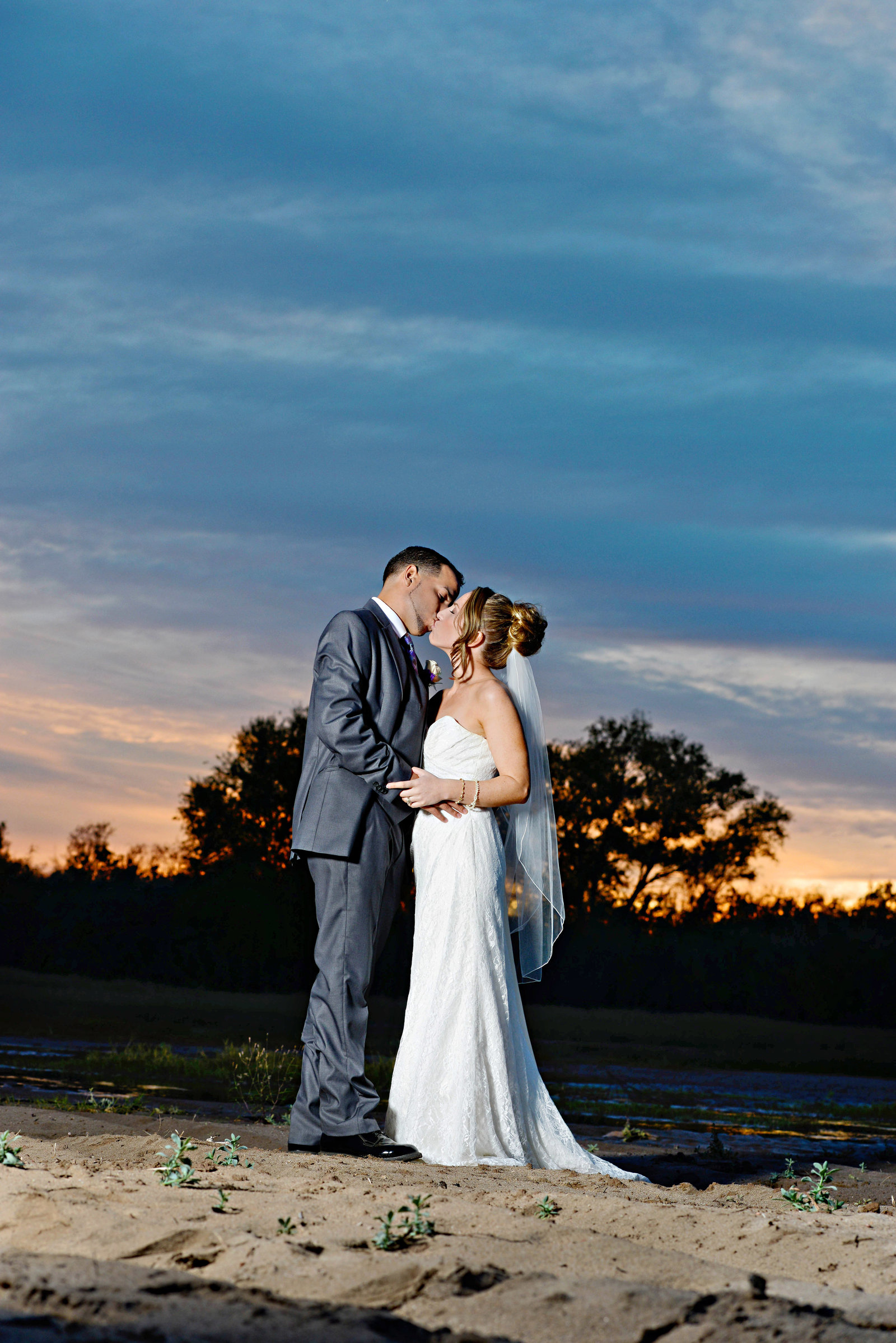 bride and groom with sunset kissing in roll arizona