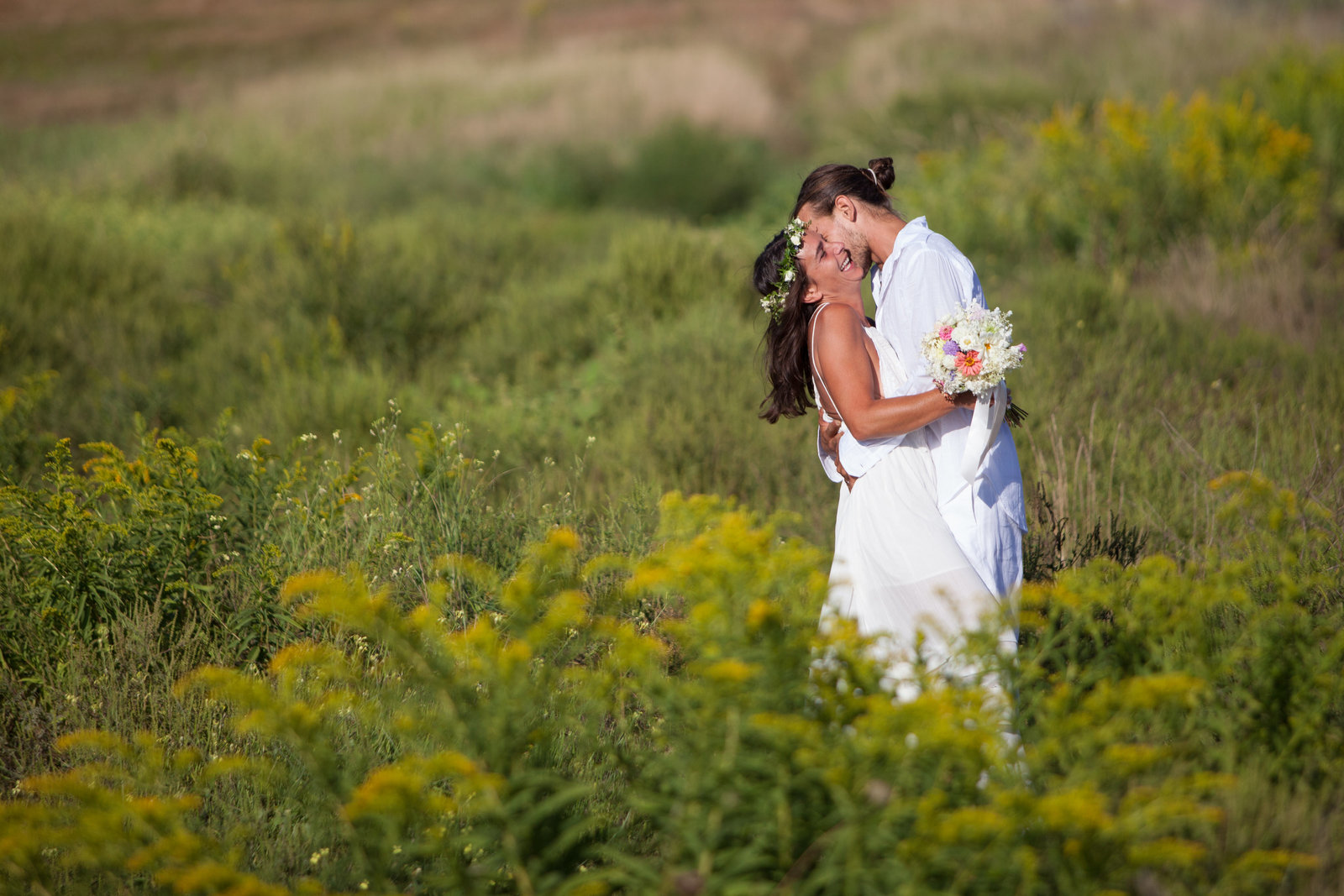 Bride and groom kissing in field of grass