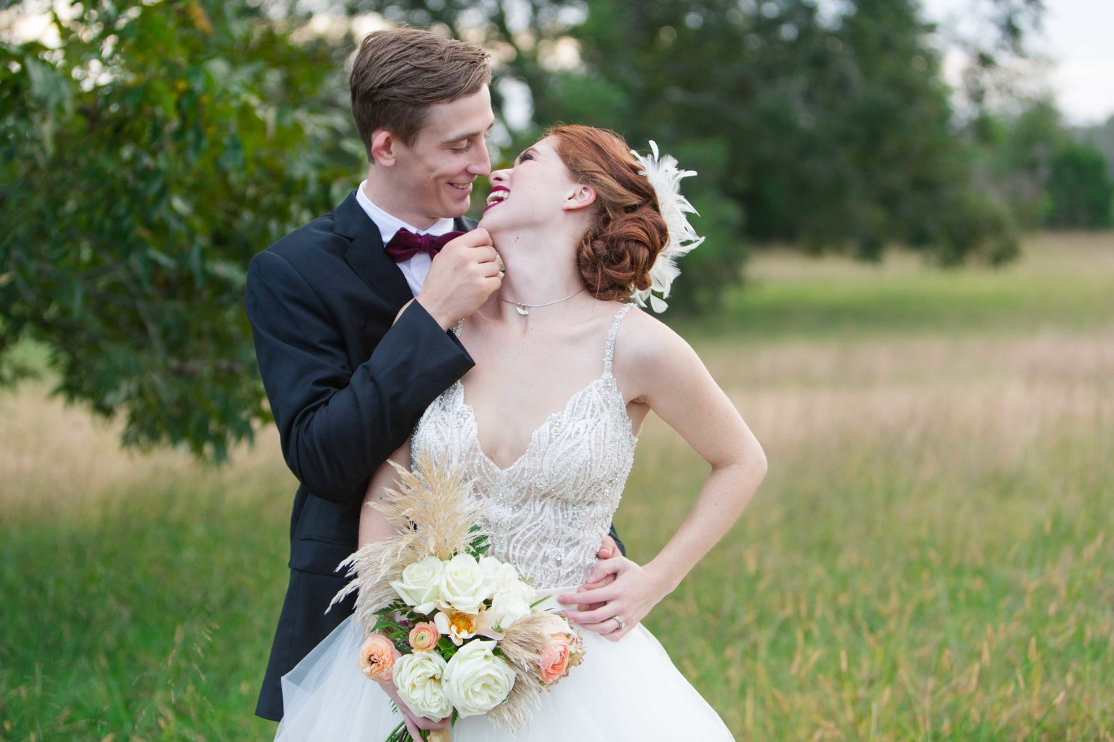 Bride and groom in a field embracing and laughing at Parterre