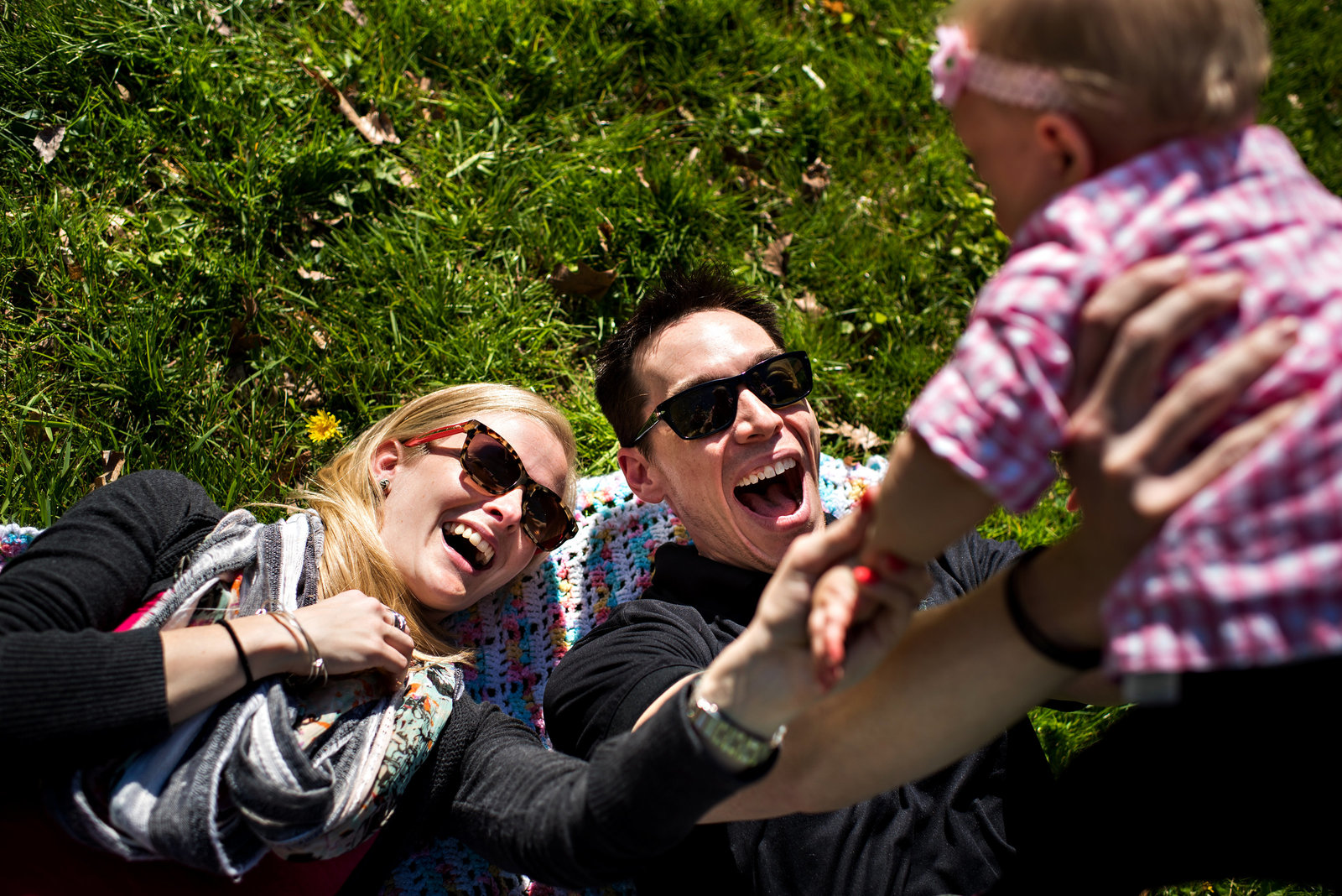 New parents lay on the grass in the park and lift their baby over their heads.