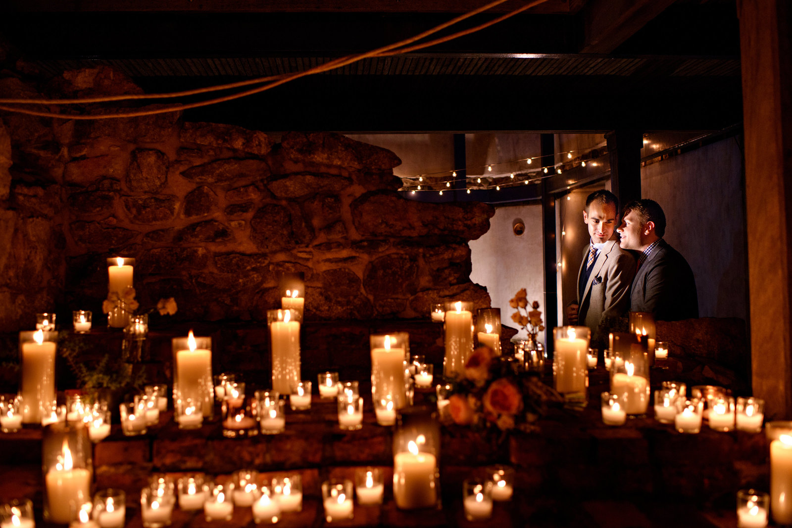 A gay wedding couple surrounded by candles at their same sex wedding.