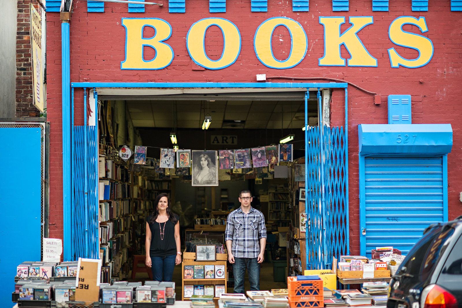 A fun couple standing in the doorway of a south philly bookstore.