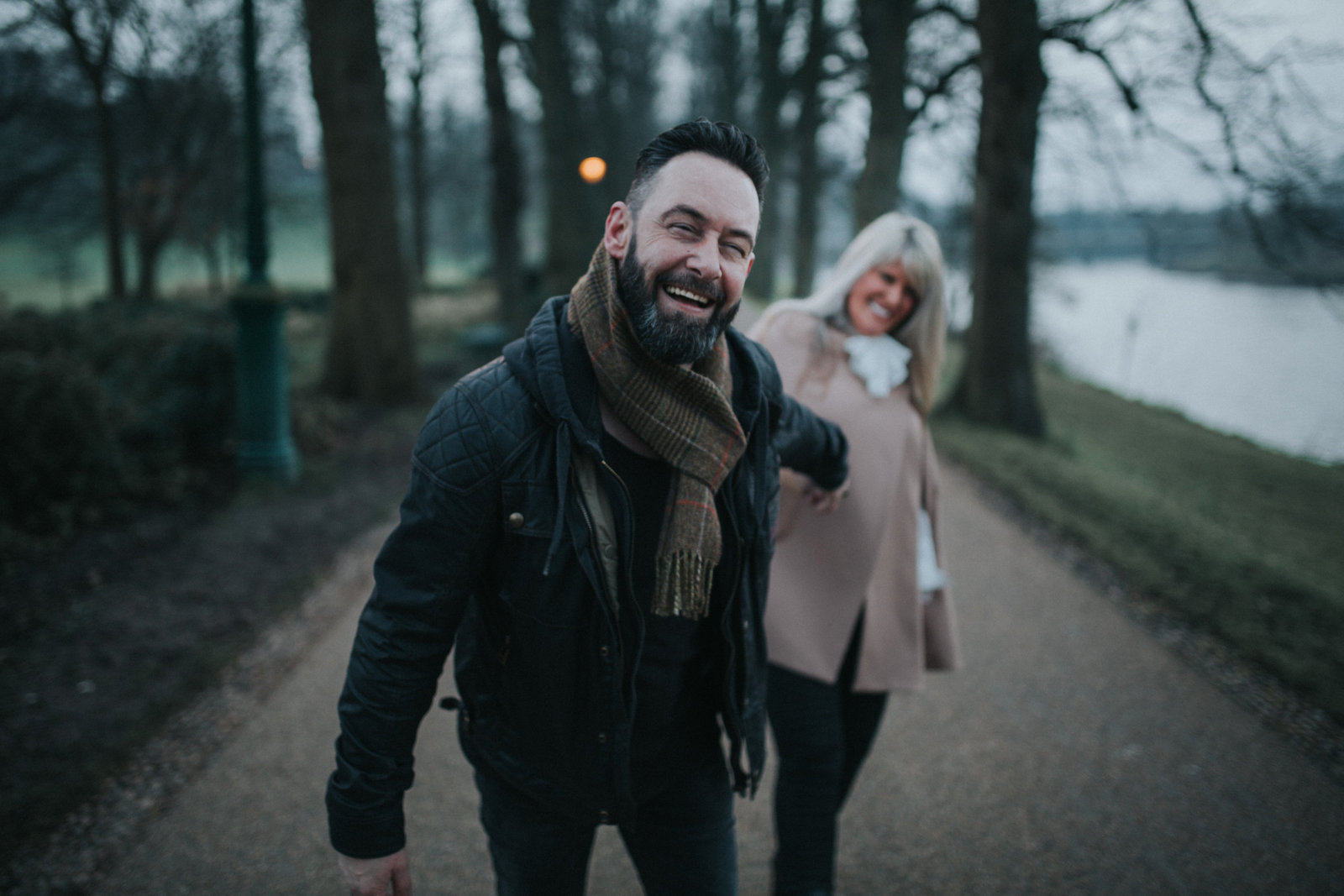 Man with beard pulling his fiancee to follow him in Prestons Averham & Miller Parks by Preston Wedding Photographer Jono Symonds