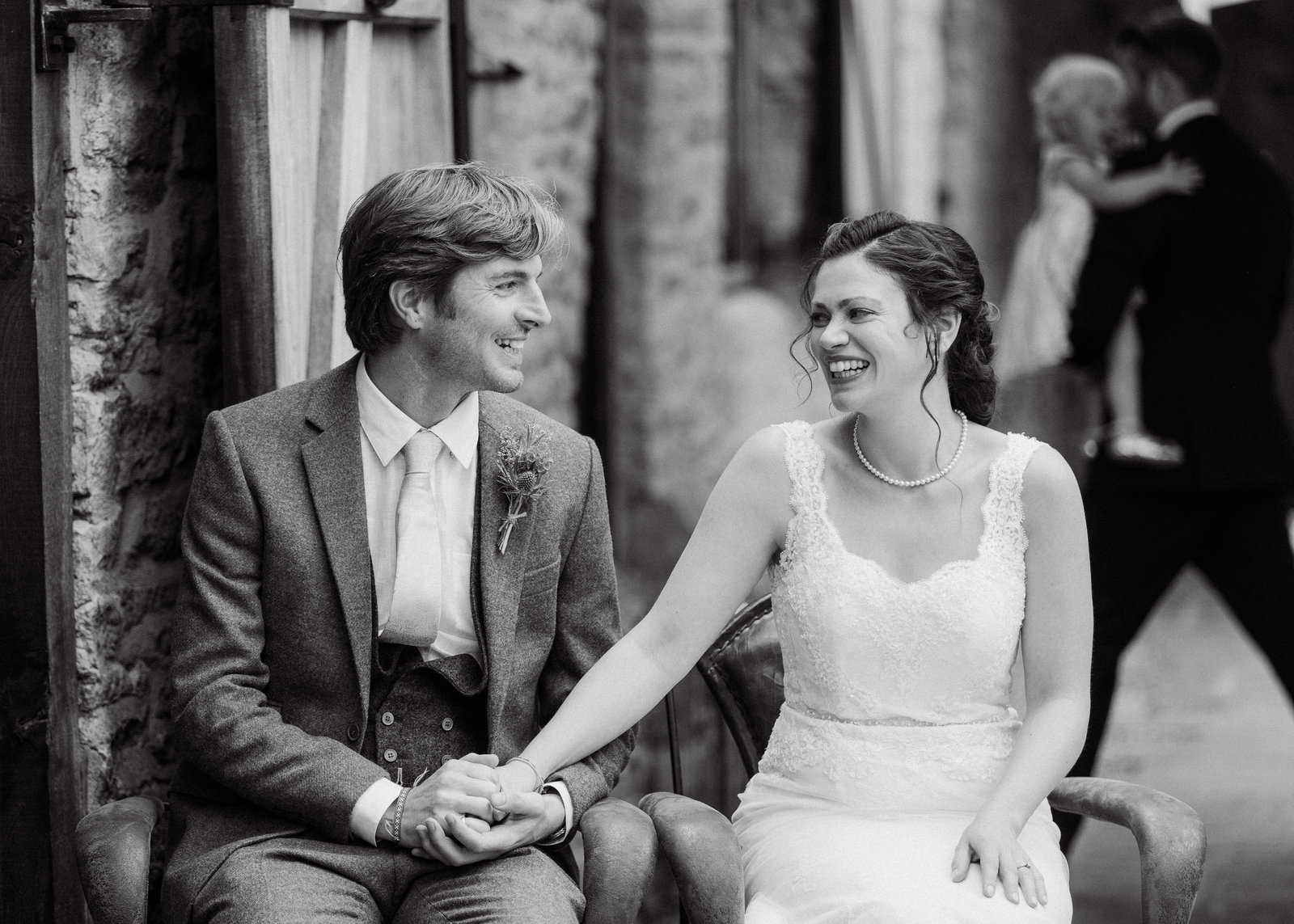 Beautiful photo of bride and groom during wedding ceremony as they lovingly look and smile at each other during a reading in their outdoor ceremony at the Tithe Barn in Launton, near Bicester