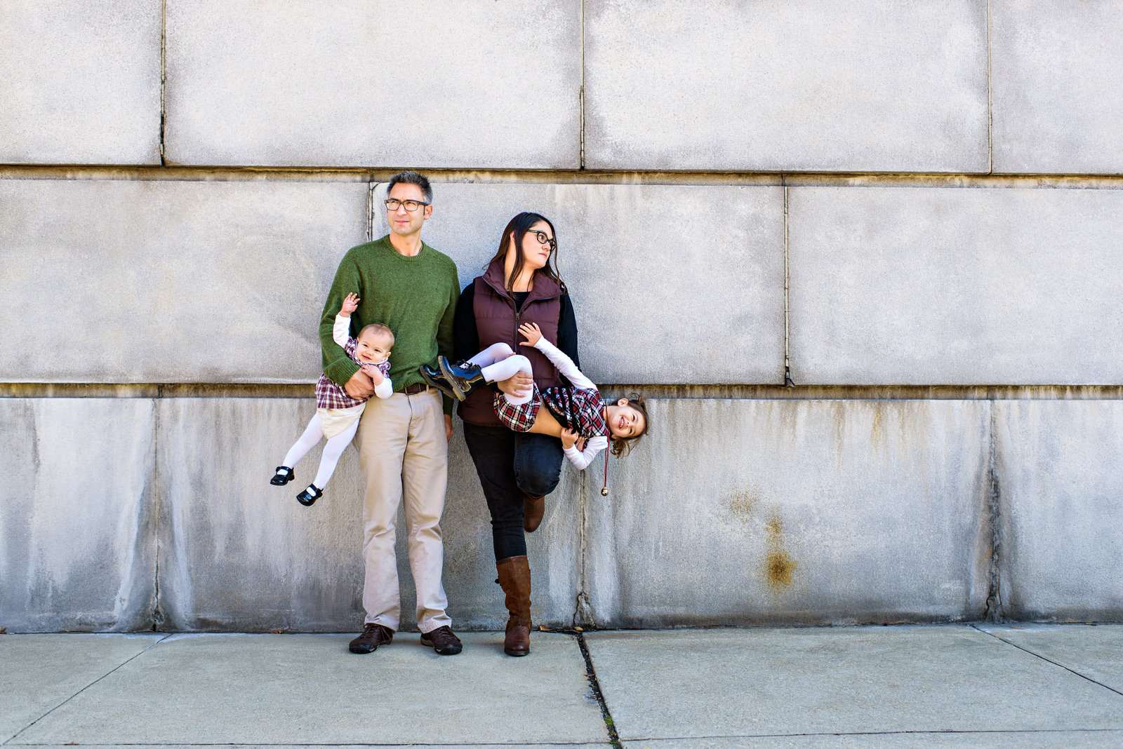 A family portrait in philly of two parents holding their two kids upside down.
