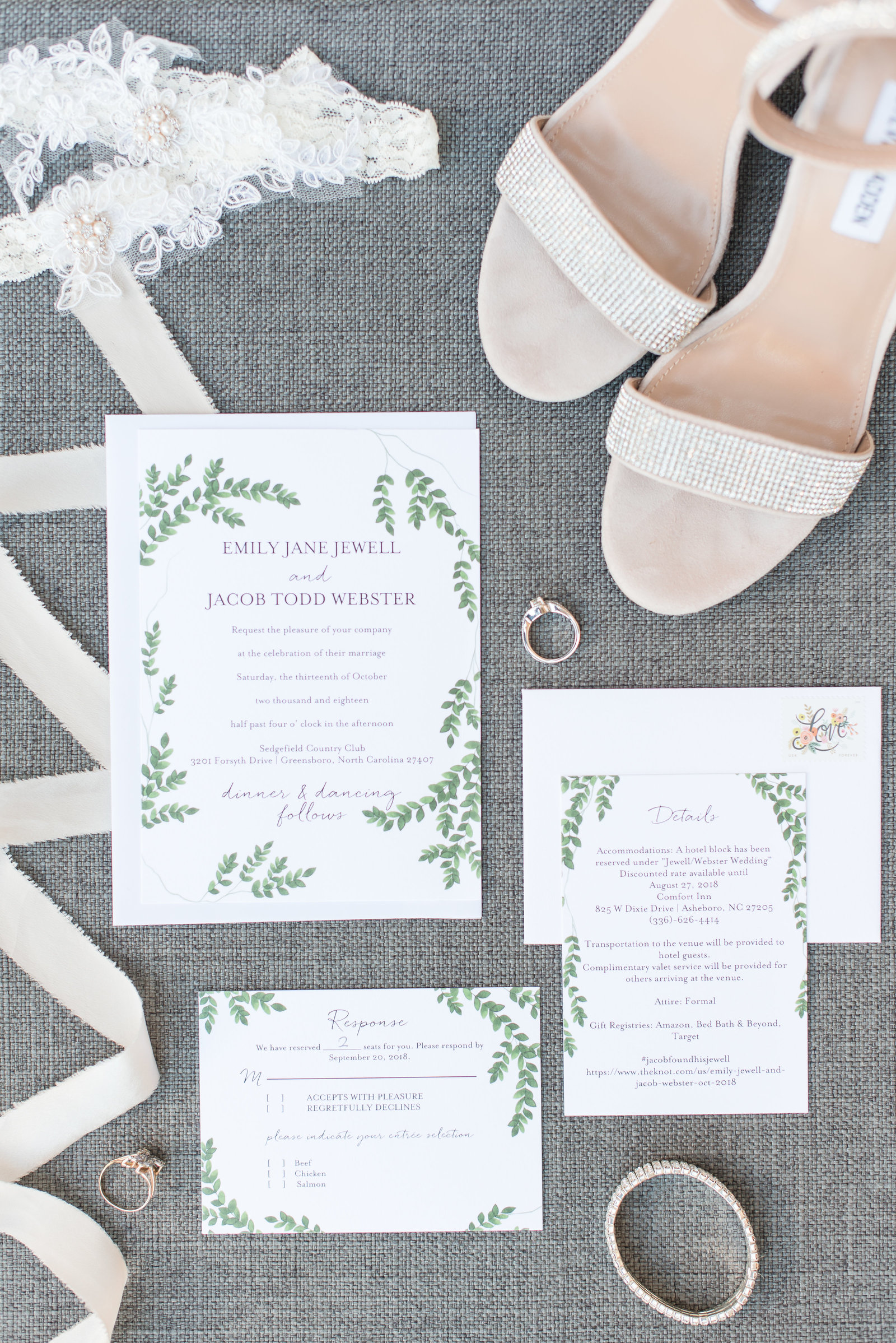white and green wedding invitation suite on top of a gray background with light pink ribbon with silver wedding jewerly with champagne wedding heels at Sedgefield Country Club