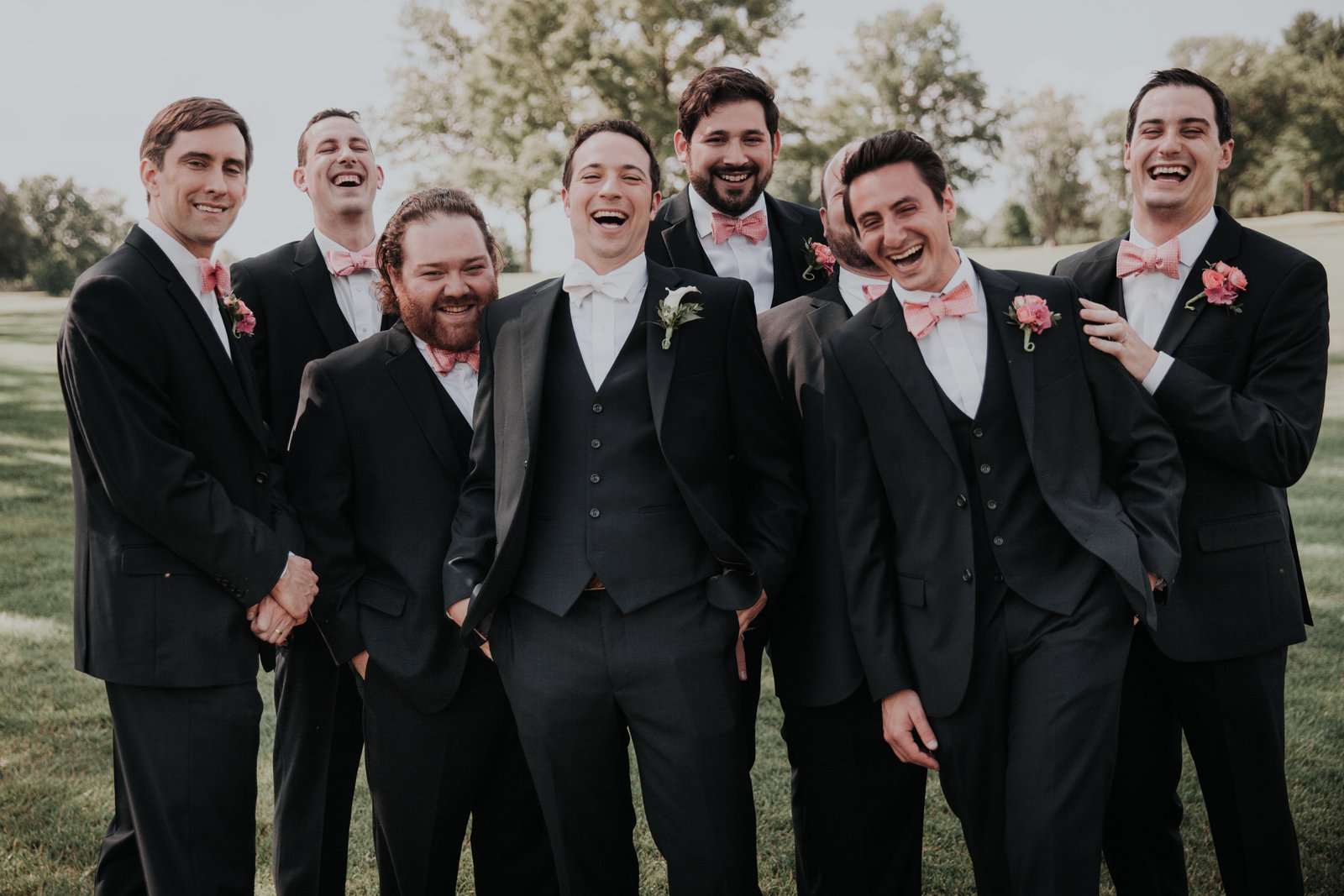 groomsmen laugh outside at their wedding