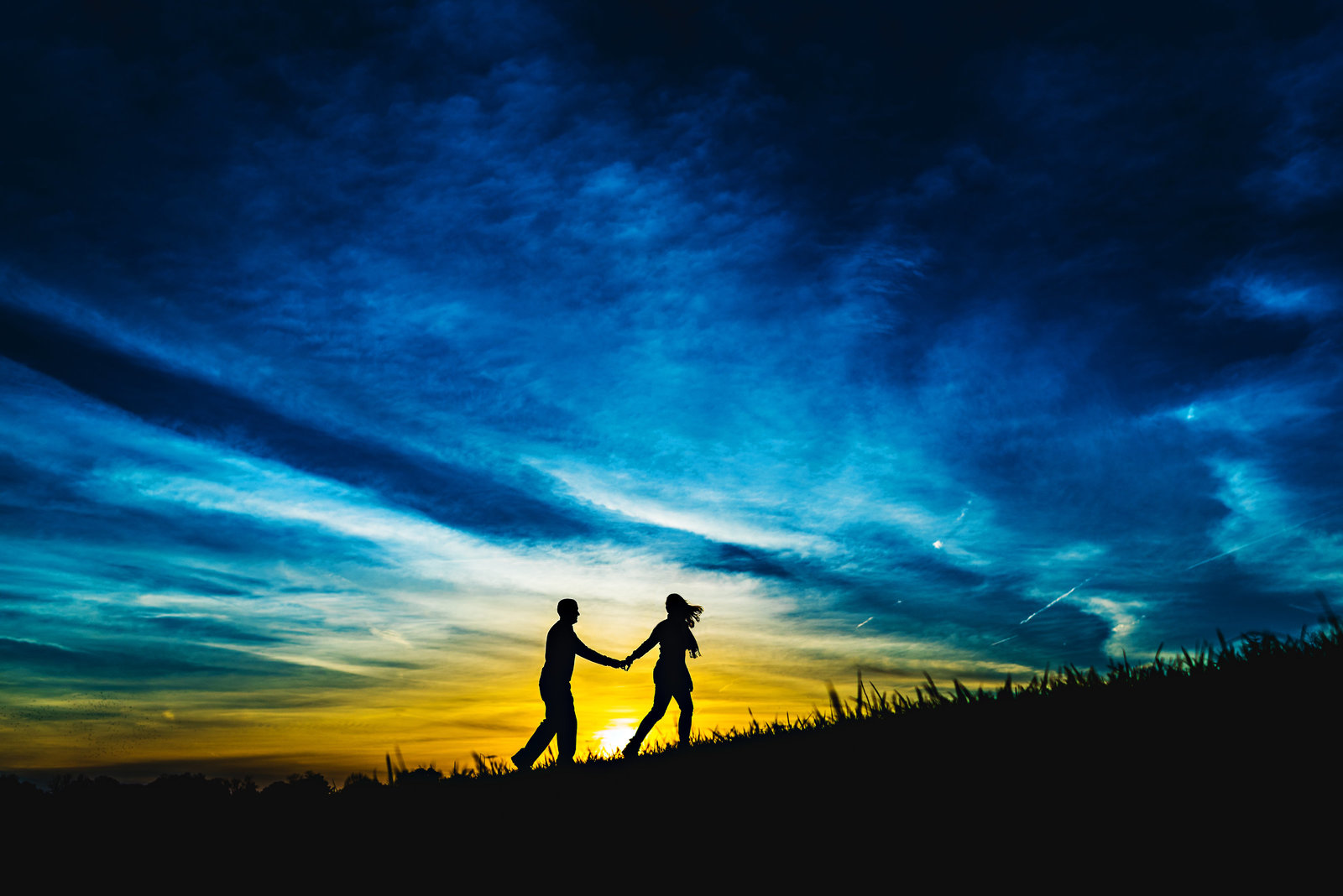 An engaged couple walk up a hill in the setting sun.