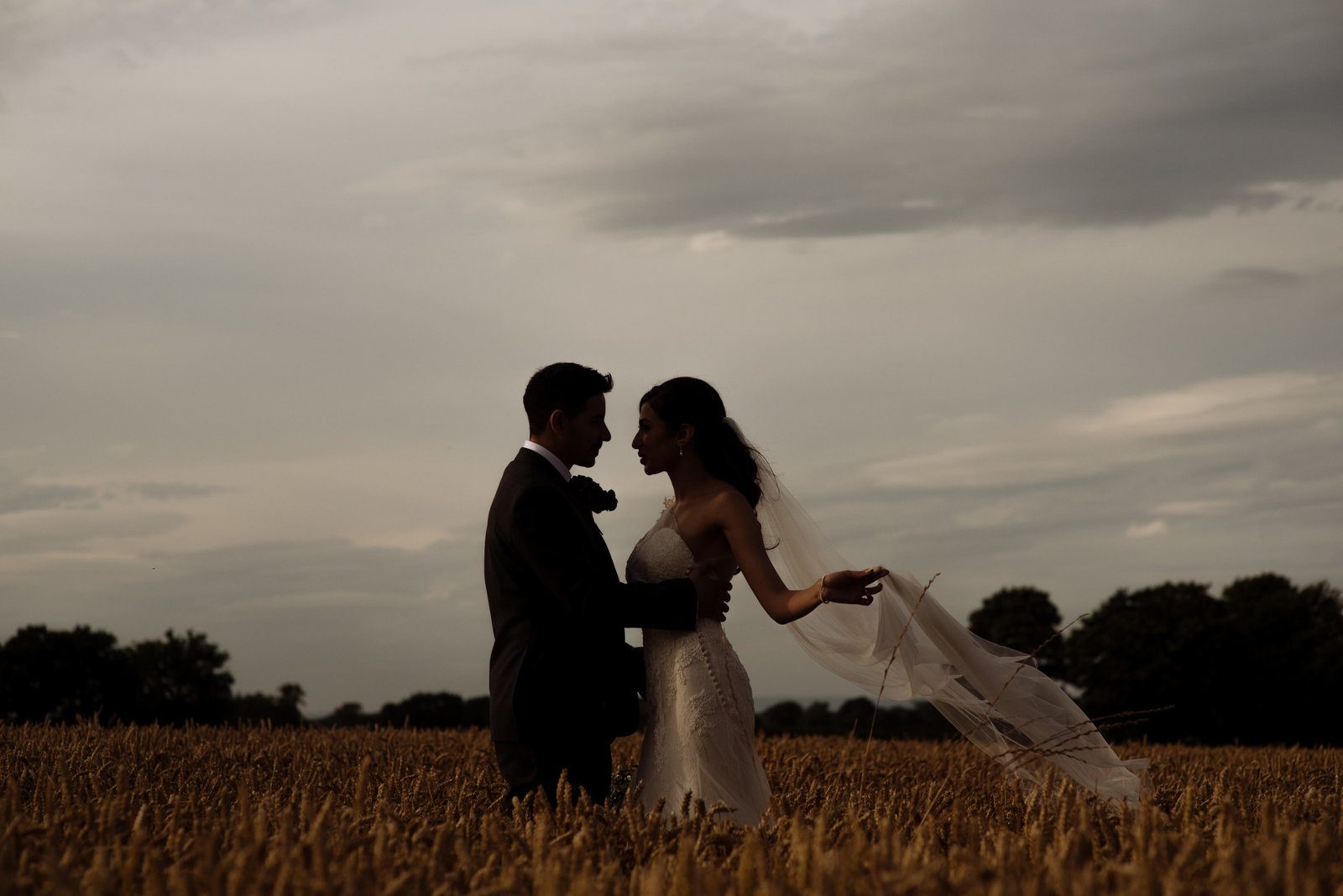 Bride and groom in wheat field at The normans Wedding venue. Contemporary wedding photographer