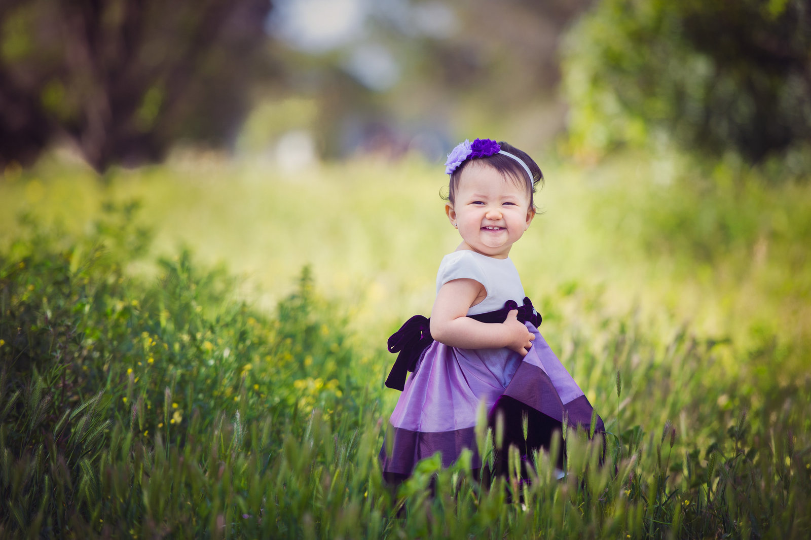 baby in purple dress in green field