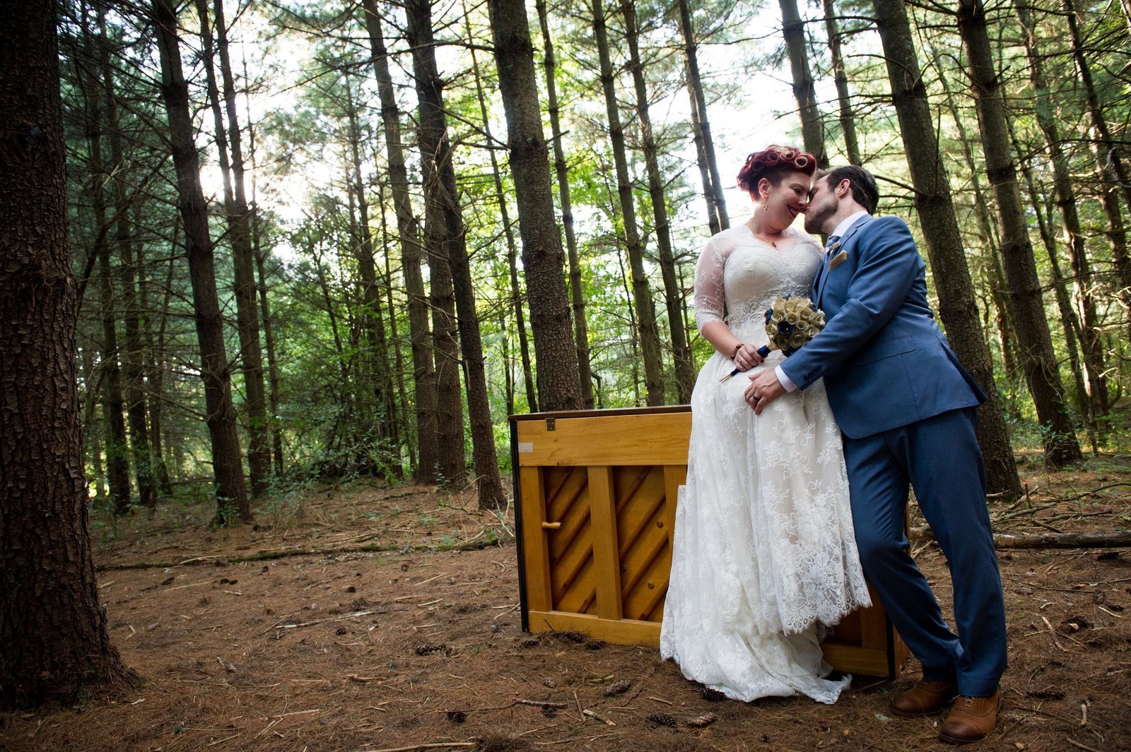 Bride and groom, just married, post on piano in forest.