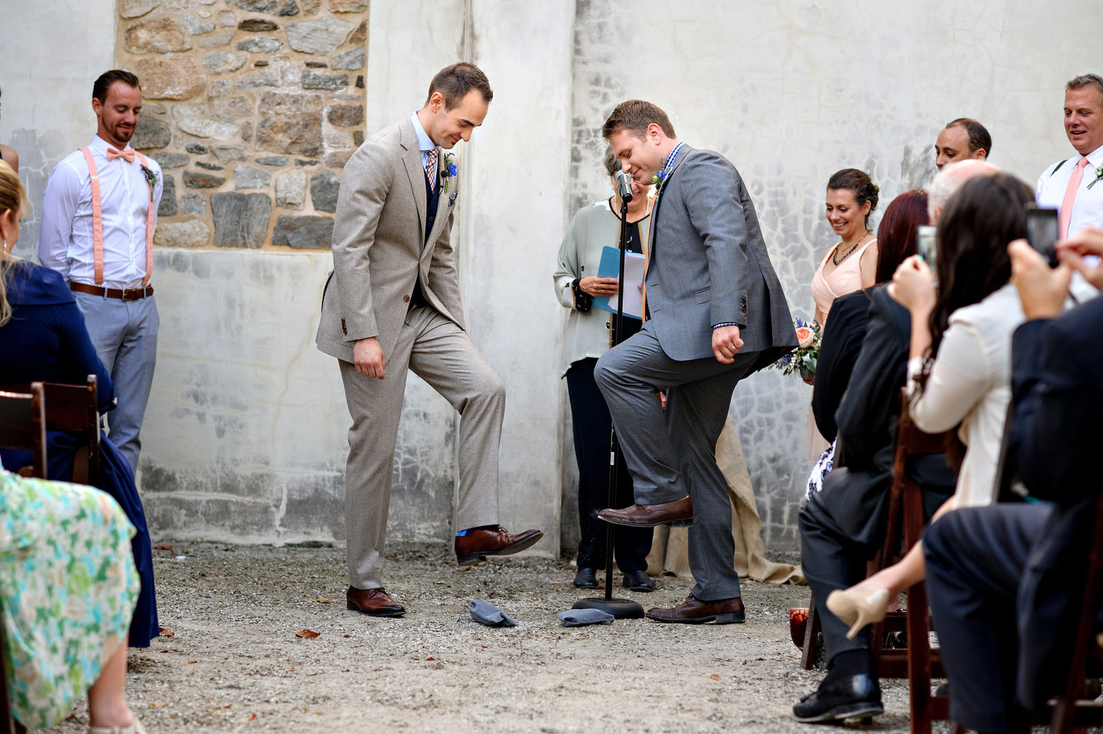 A same sex wedding couple during their jewish ceremony tradition of smashing of the glass.