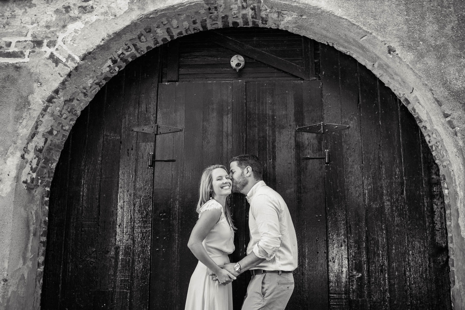 Engaged couple stand under arched door in Dueler's Alley, Downtown Charleston, South Carolina