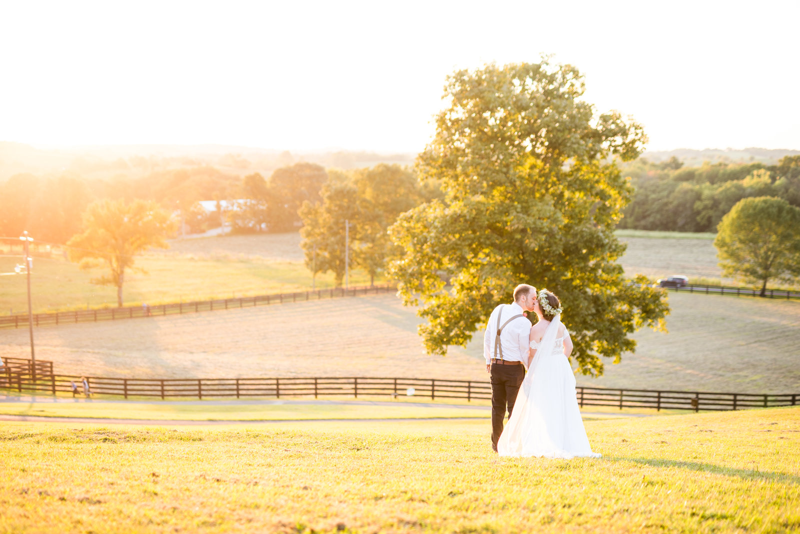 Groom-kissing-bride-on-forhead-during-golden-hour-at-their-fall-farm-wedding-in-dayton-ohio