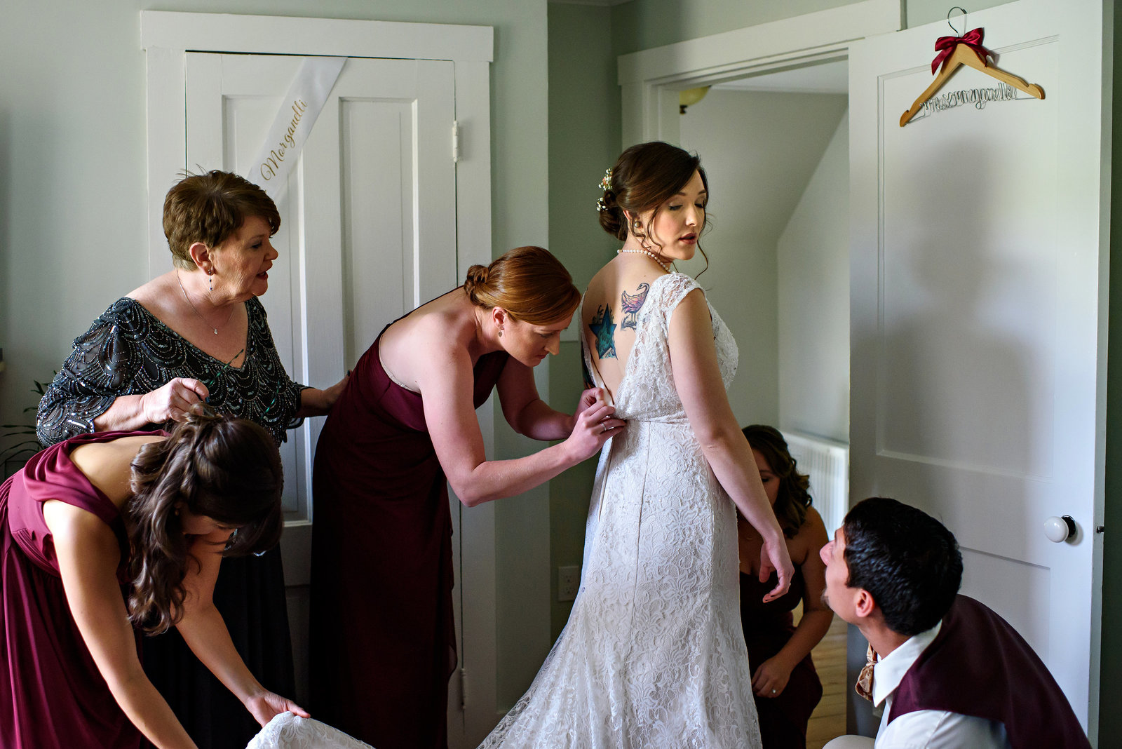 A bridal party helps bride get ready for the outside ceremony at this destination wedding in New Hampshire.