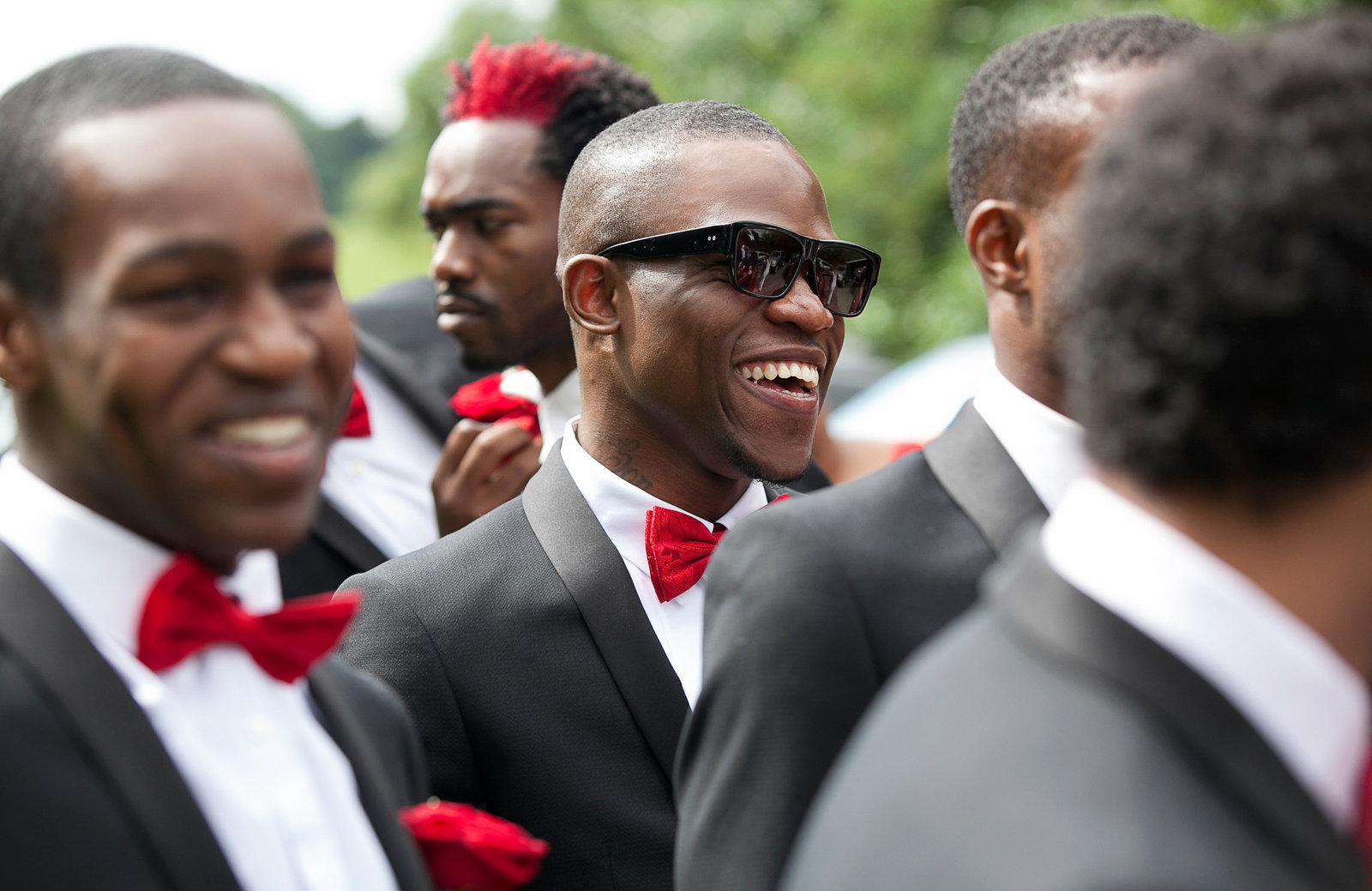 Candid natural photo of these stylish groomsmen in black suit with red bow tie at this nigerian wedding in London