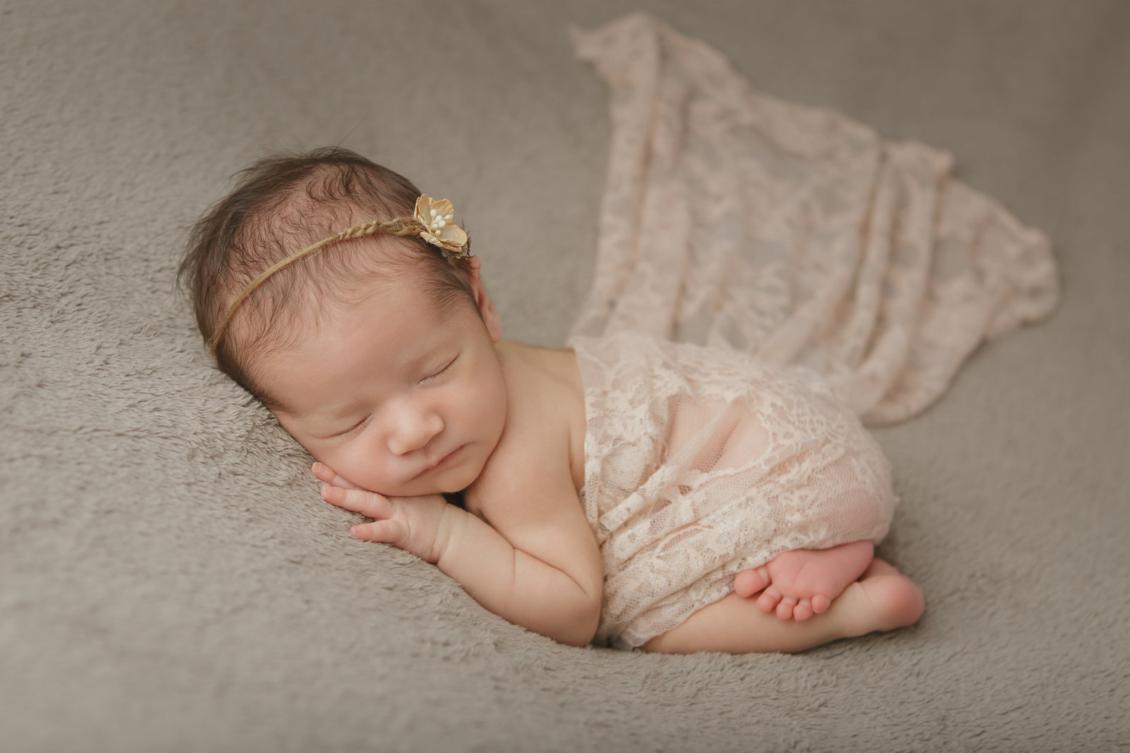 sleeping newborn baby girl with neutral earth tones, lace wrap and headband in a cute pose by Hudson Valley professional photographer in Cornwall NY photography studio