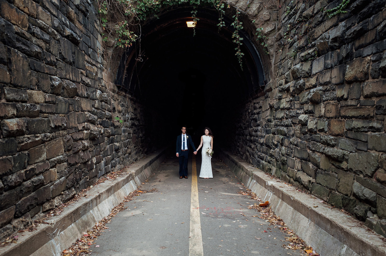 Bride and Groom pose in a tunnel