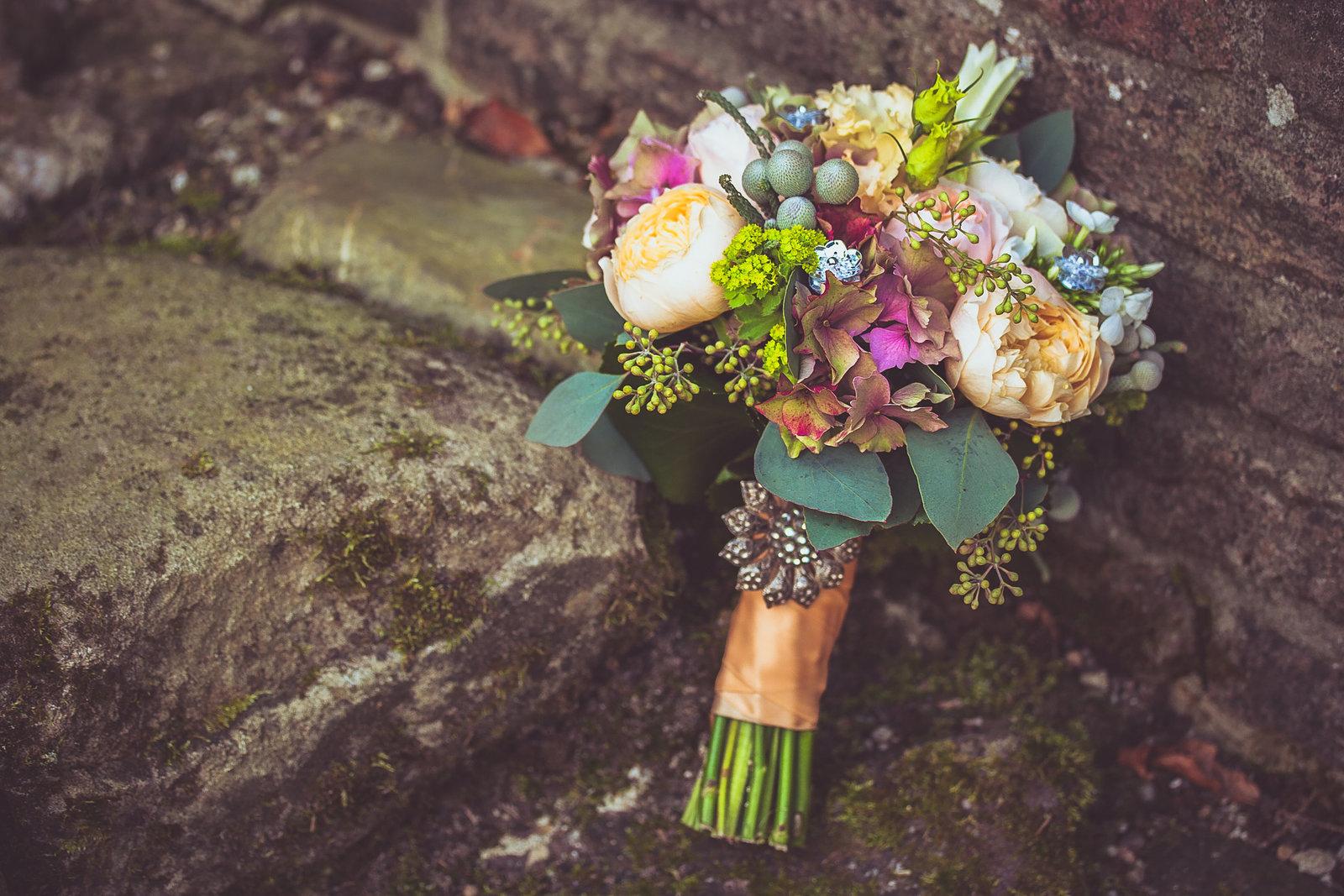 Een detailfoto op je bruiloft: een schitterend bruidsboeket met pioenrozen en een mooie broche. Copyright Nanda Zee-Fritse | FOTOZEE