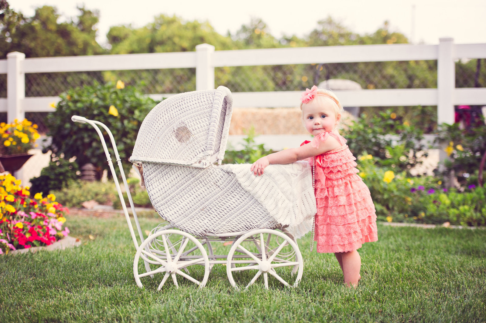 little girl in peach jumper with vintage baby carriage