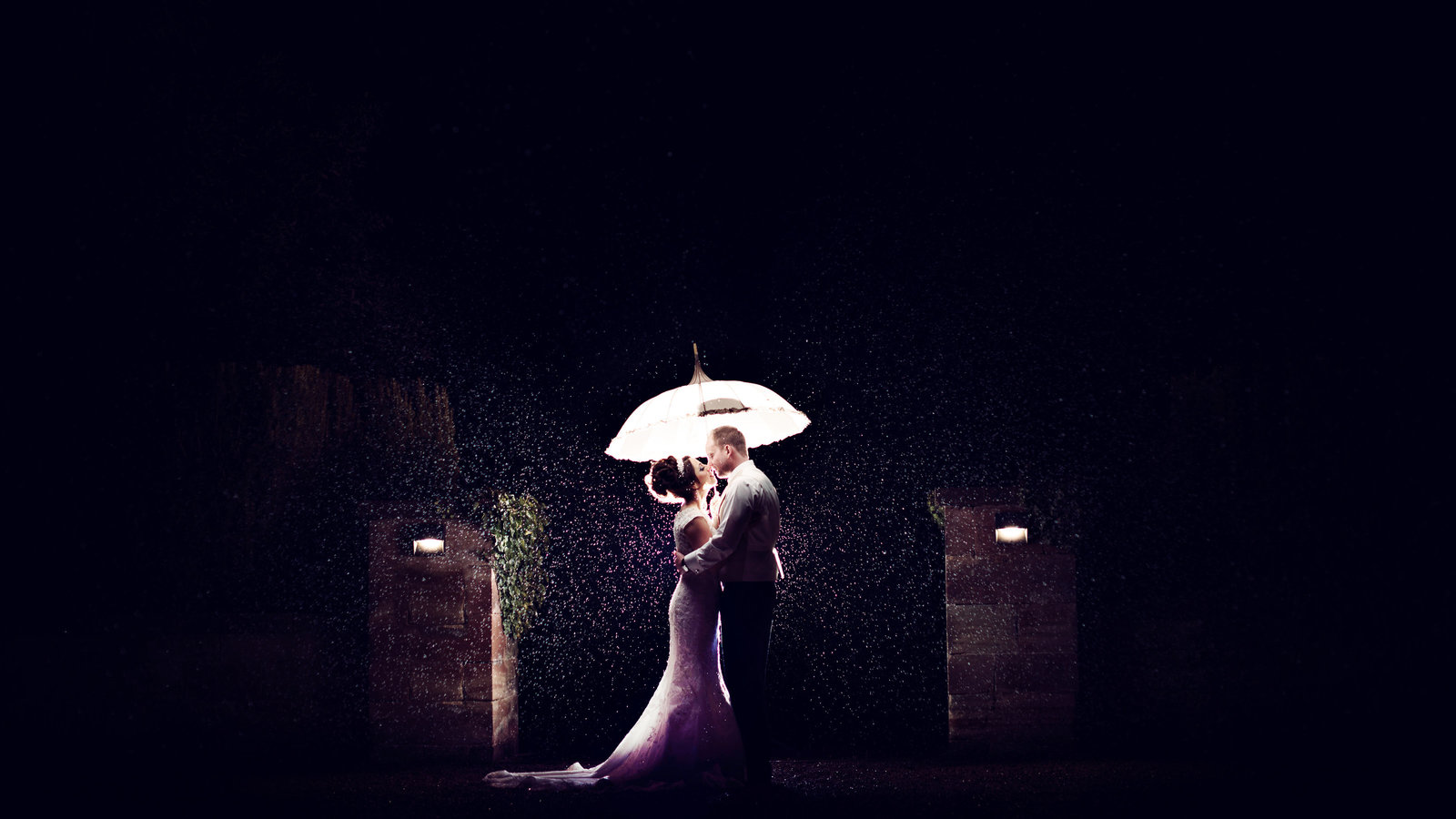 Bride and Groom stand in the rain on their wedding day at Inglewood Manor in Cheshire