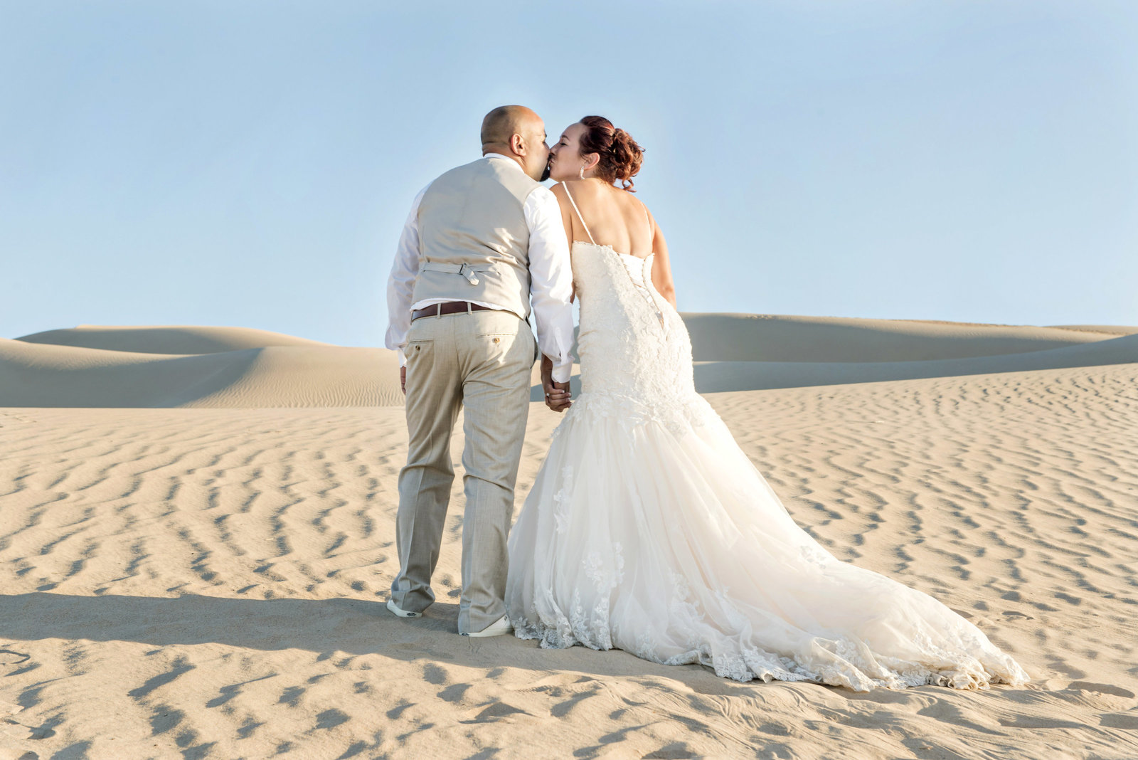 bride and groom kissing on sand dune