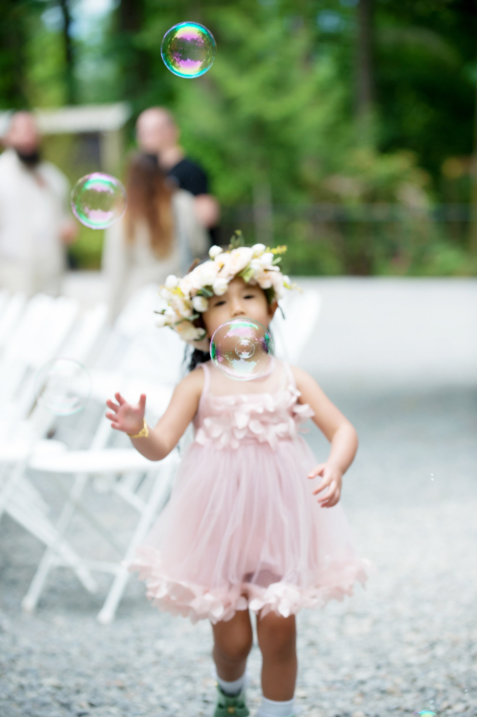 flower girl chases bubbles
