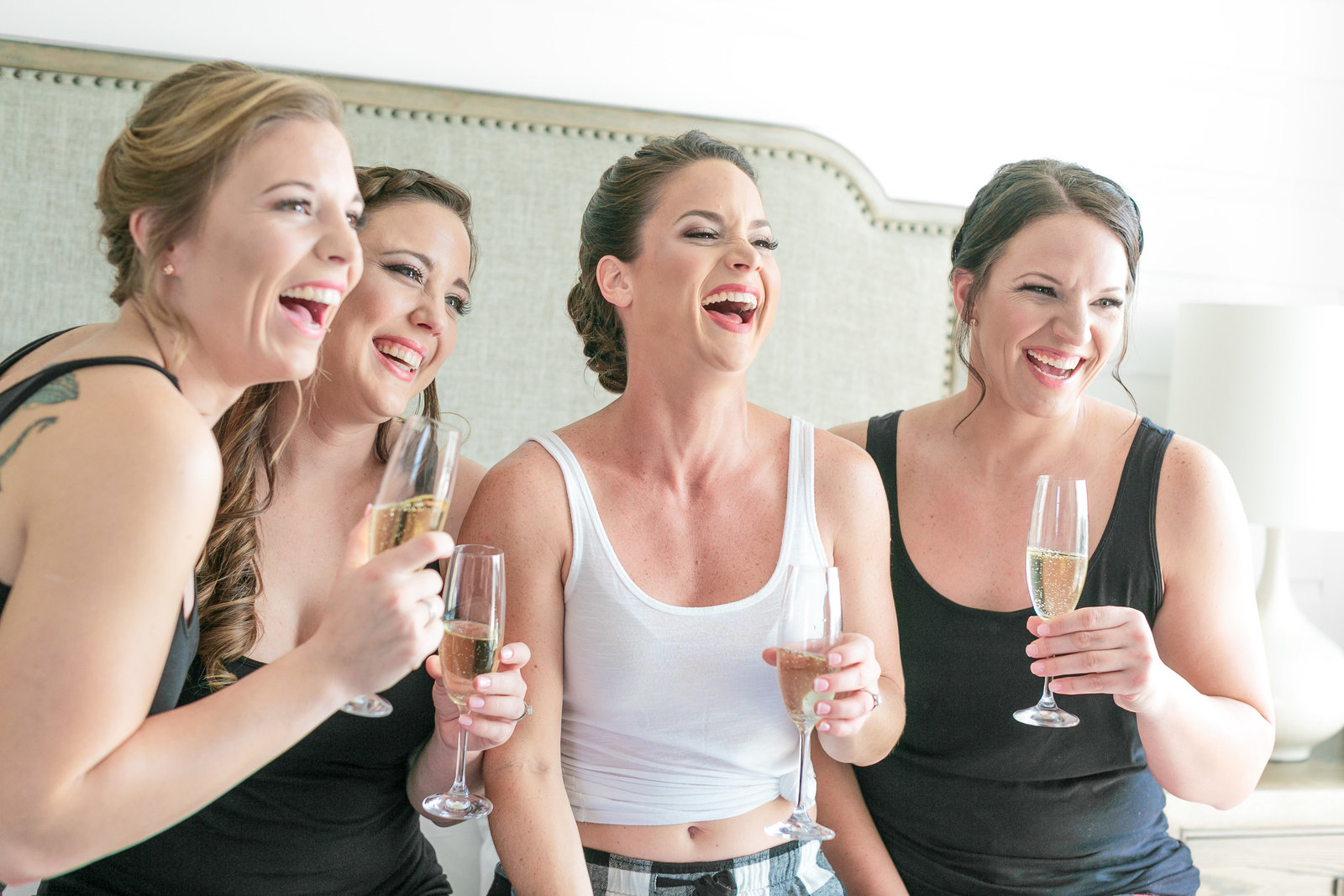 Girls sitting on the bed laughing with wine glasses in their hands