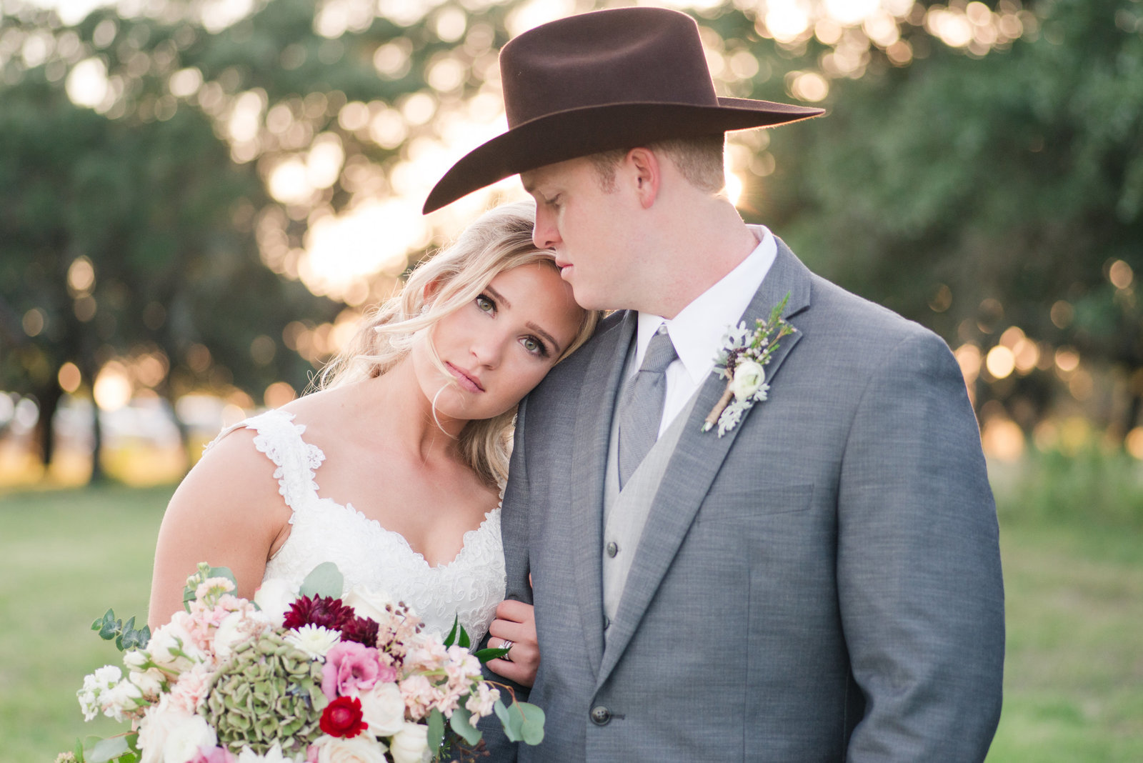 Bride leans on groom's shoulder wearing a cowboy hat at CW Hill Country Ranch in Boerne
