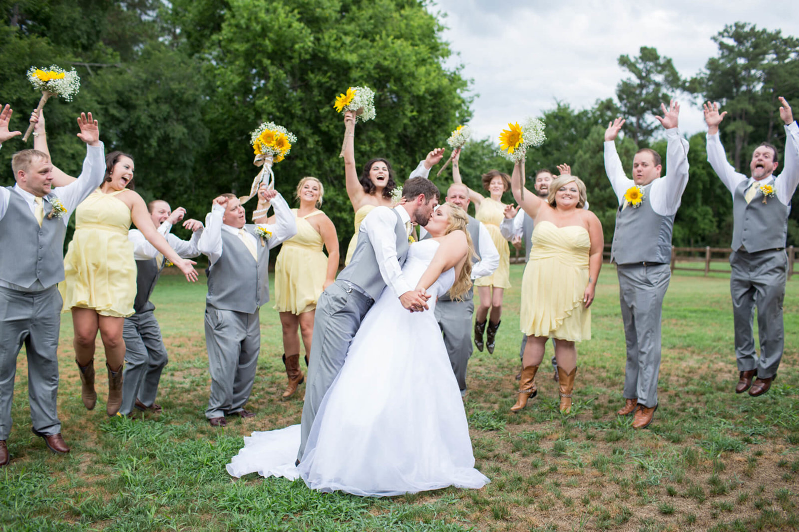 bride and groom kiss bridal party jumping