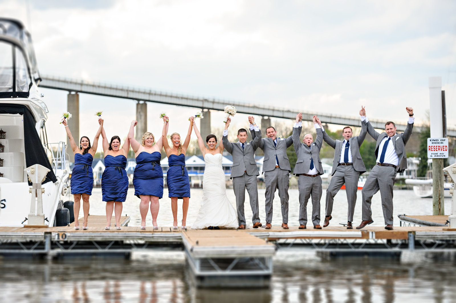 A happy wedding party cheer for joy on the docks outside of the Chesapeake Inn Restaurant.