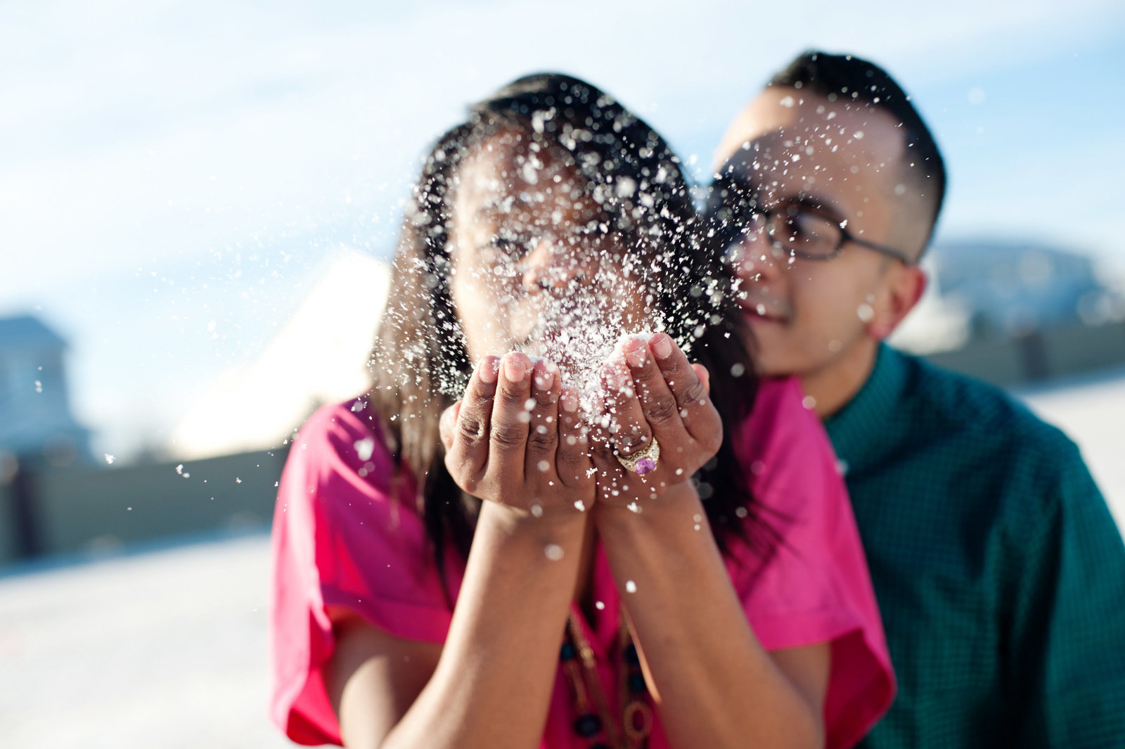 a girl blows snow out of her hand into the camera as her fiance watches in great falls montana
