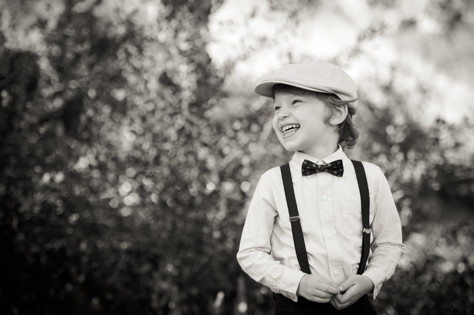 black and white photograph of laughing boy with suspenders and bow tie