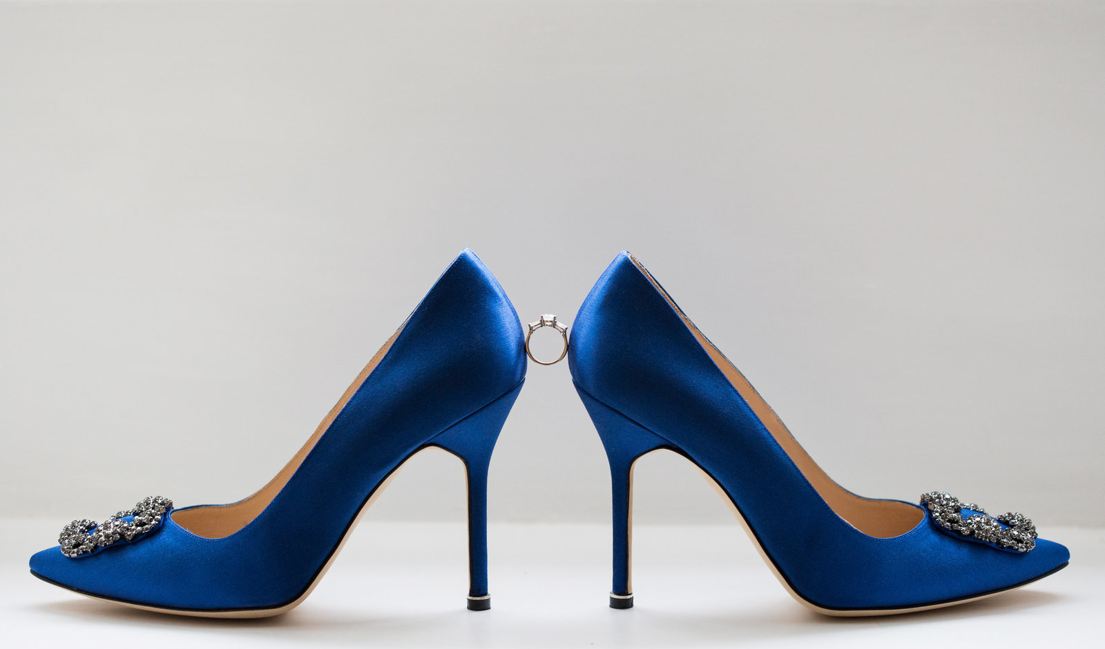 Stunning side on view of these something blue  Manolo Blahnik wedding shoes with engagement ring balancing between the shoes. Captured by Nicci at Adorlee