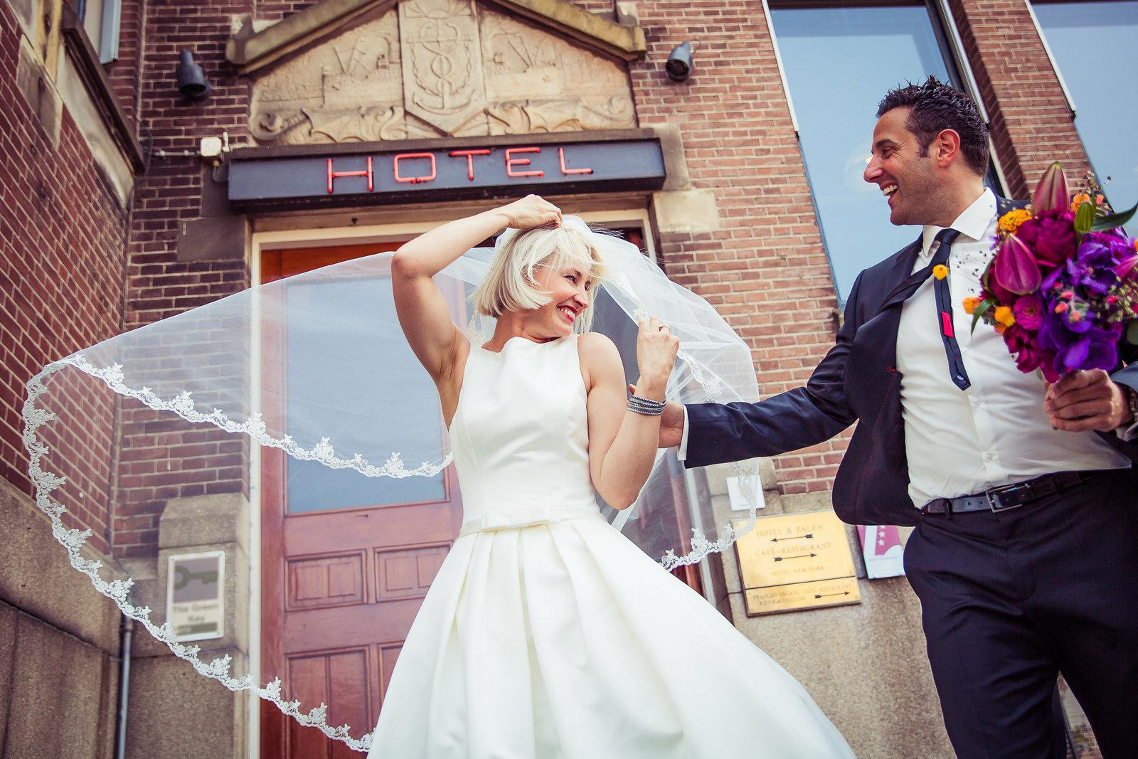 De sluier van de bruid vangt wind. Bruidegom heeft trouwboeket in handen met verschillende bloemen  in roodtinten. Hotel New York Rotterdam Copyright Nanda Zee-Fritse | FOTOZEE