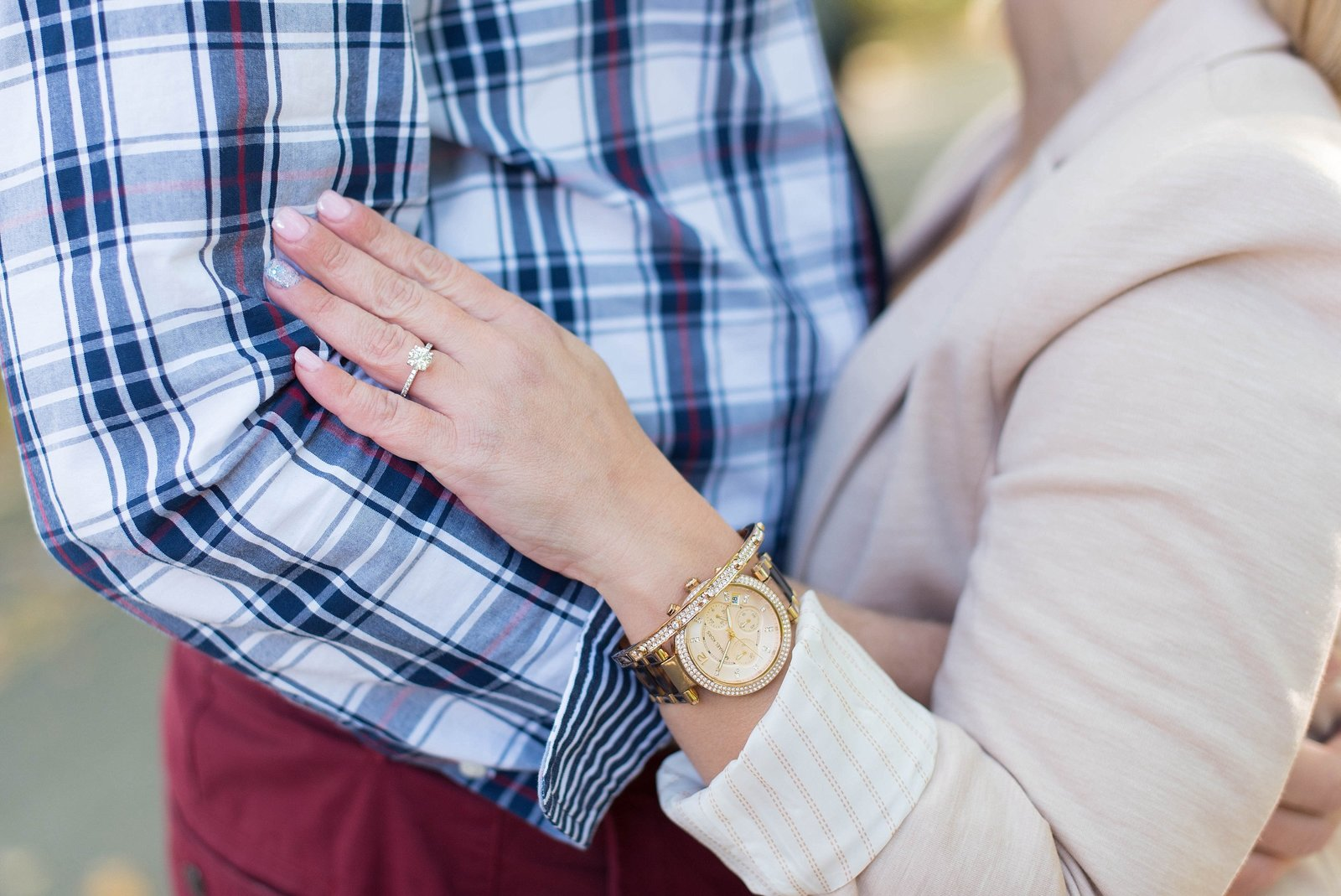 Detail shot of bride wearing silver engagement ring and gold bracelet and watch photo