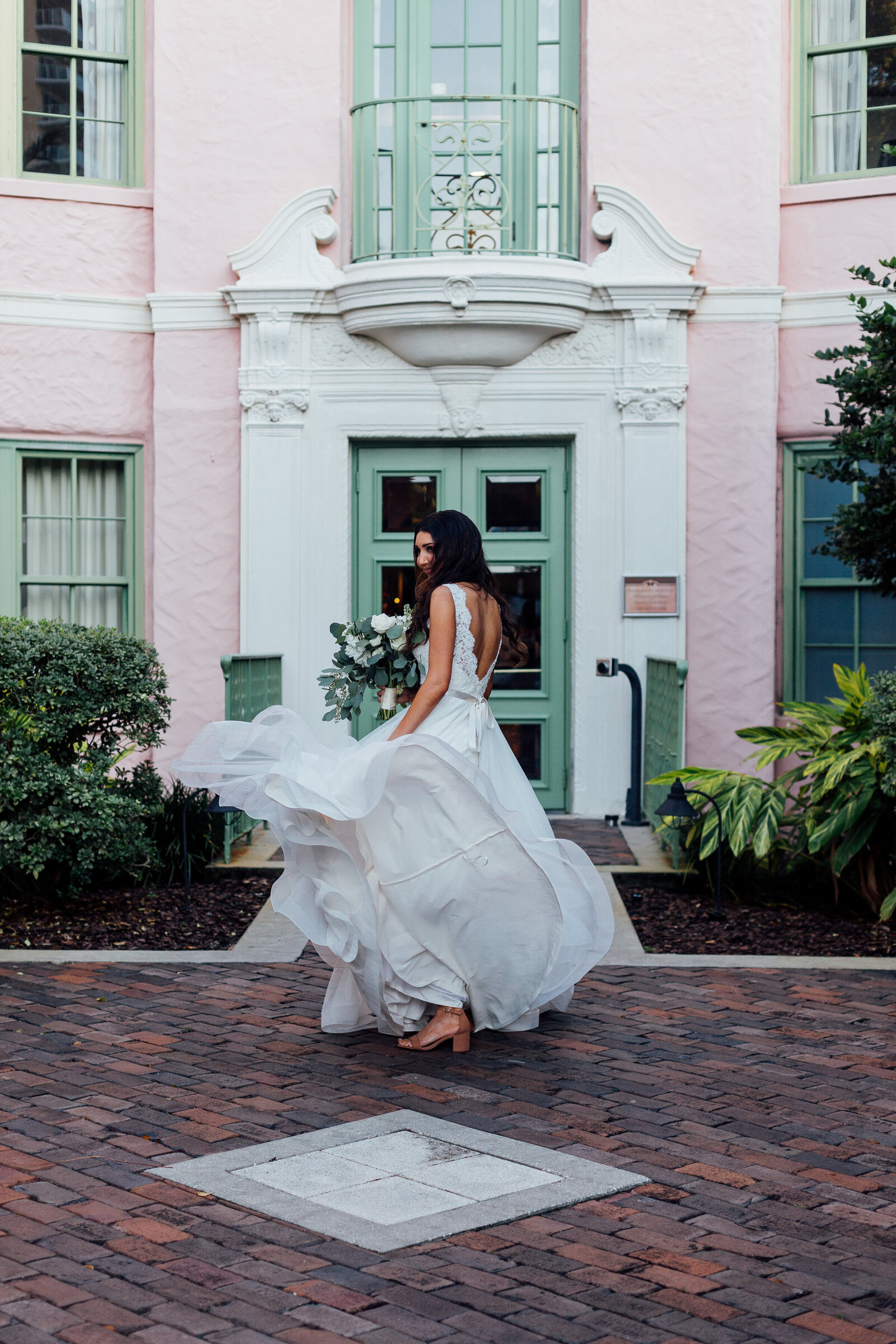 bride-walking-with-flowing-dress-into-pink-house-in-florida-photo-iris-and-urchin-ryley