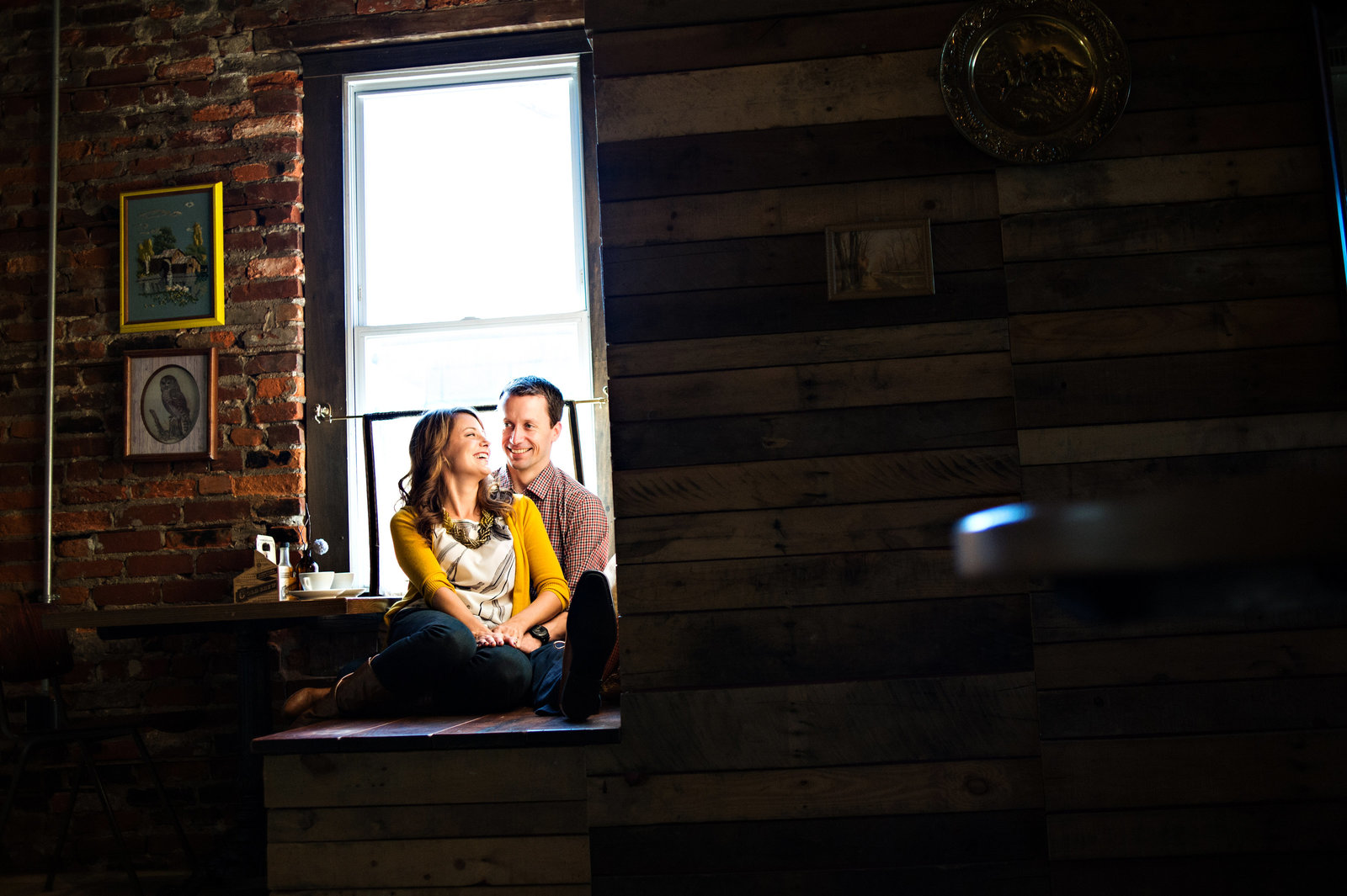 A couple sit in the window light at one shot coffee in northern liberties.