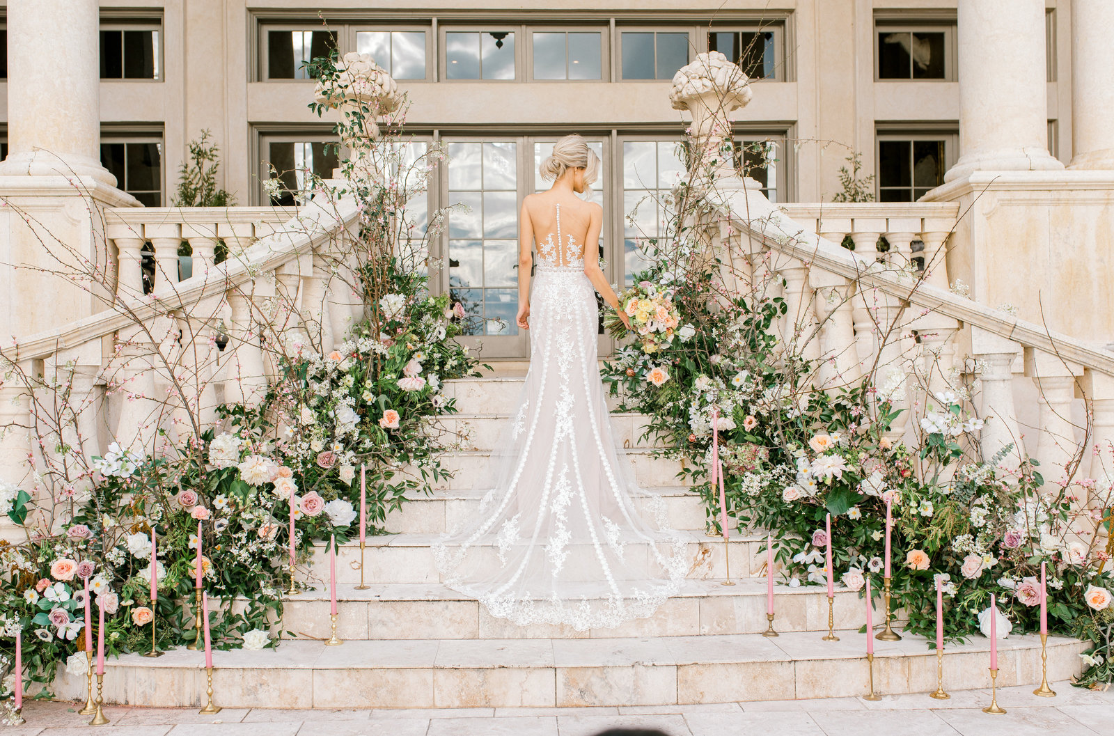 bride on stairs with a long train dress and flowers