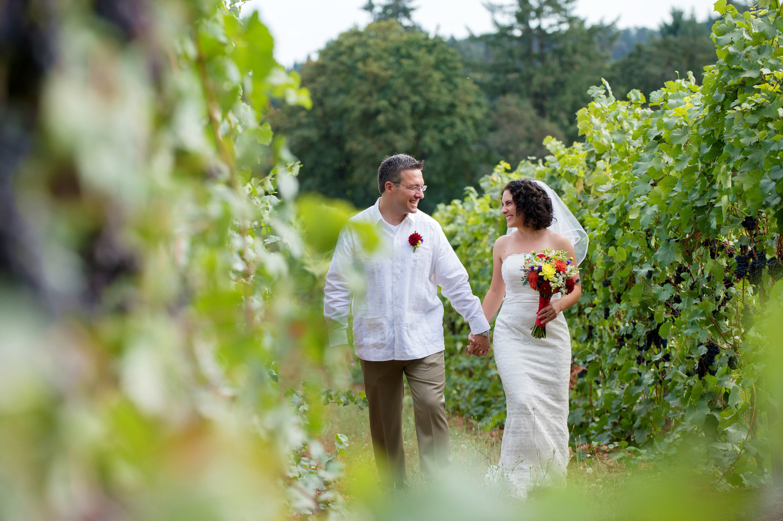 a newly married couple walk through a vineyard