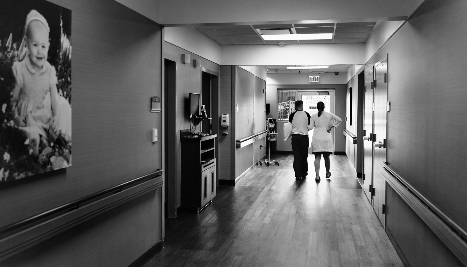 charlotte birth photographer jamie lucido documents mother and father walking in the hallways of a hospital during labor