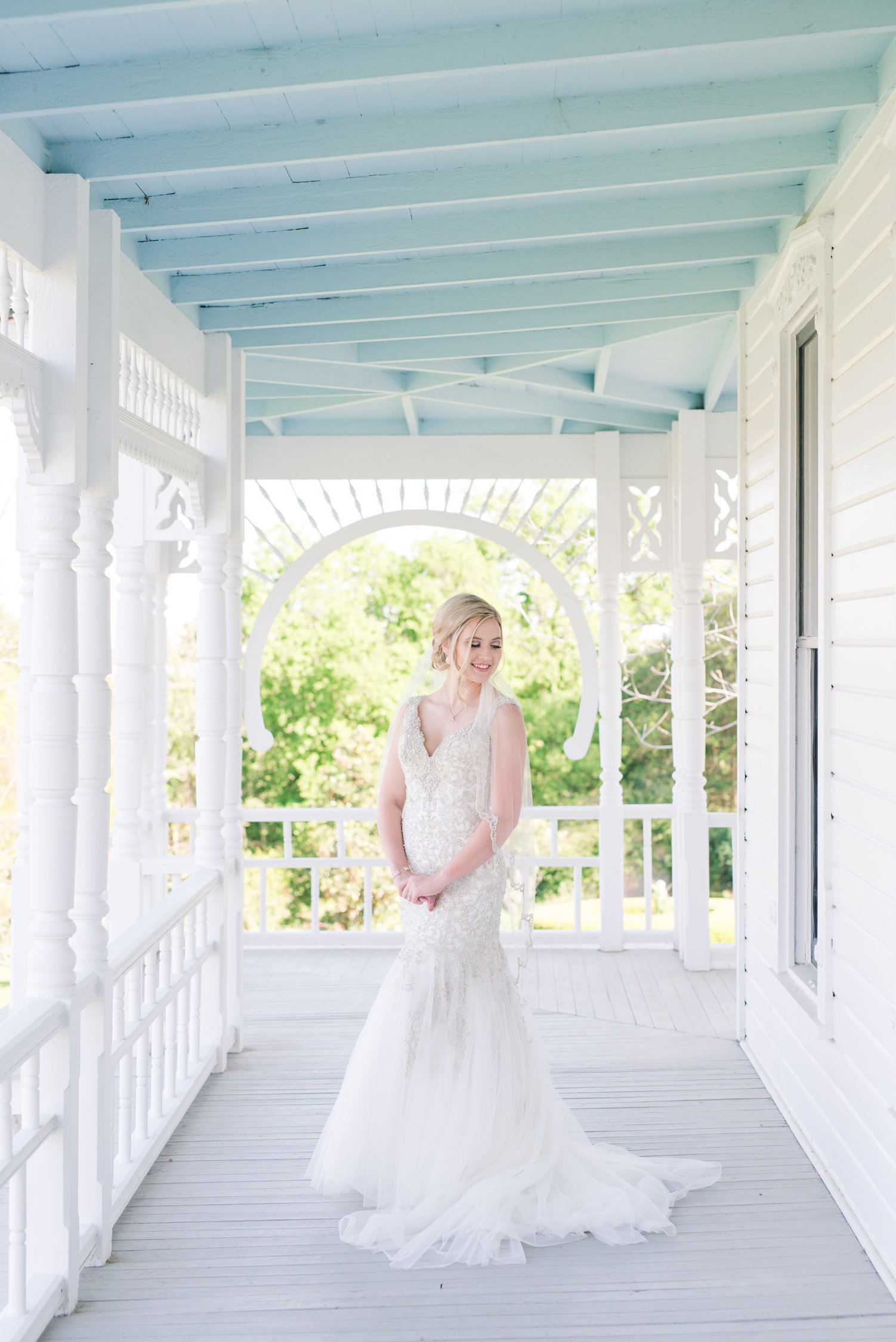 Barr Mansion Bride stands on balcony for portrait with veil