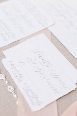 Wedding invitations with rough edges and a silver necklace with diamonds